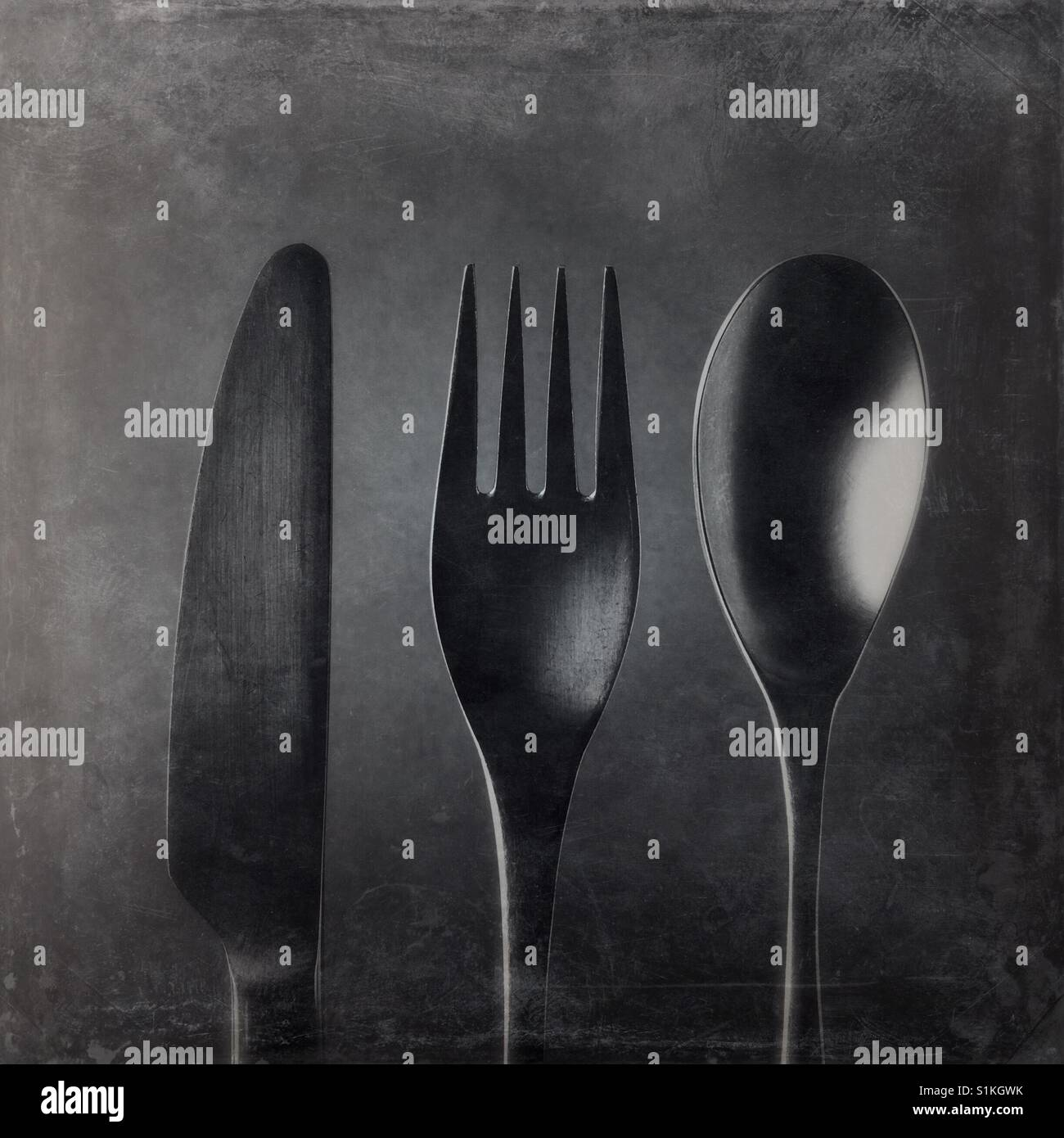 A black and white close up overhead shot of a knife and a fork and a spoon - Stock Image