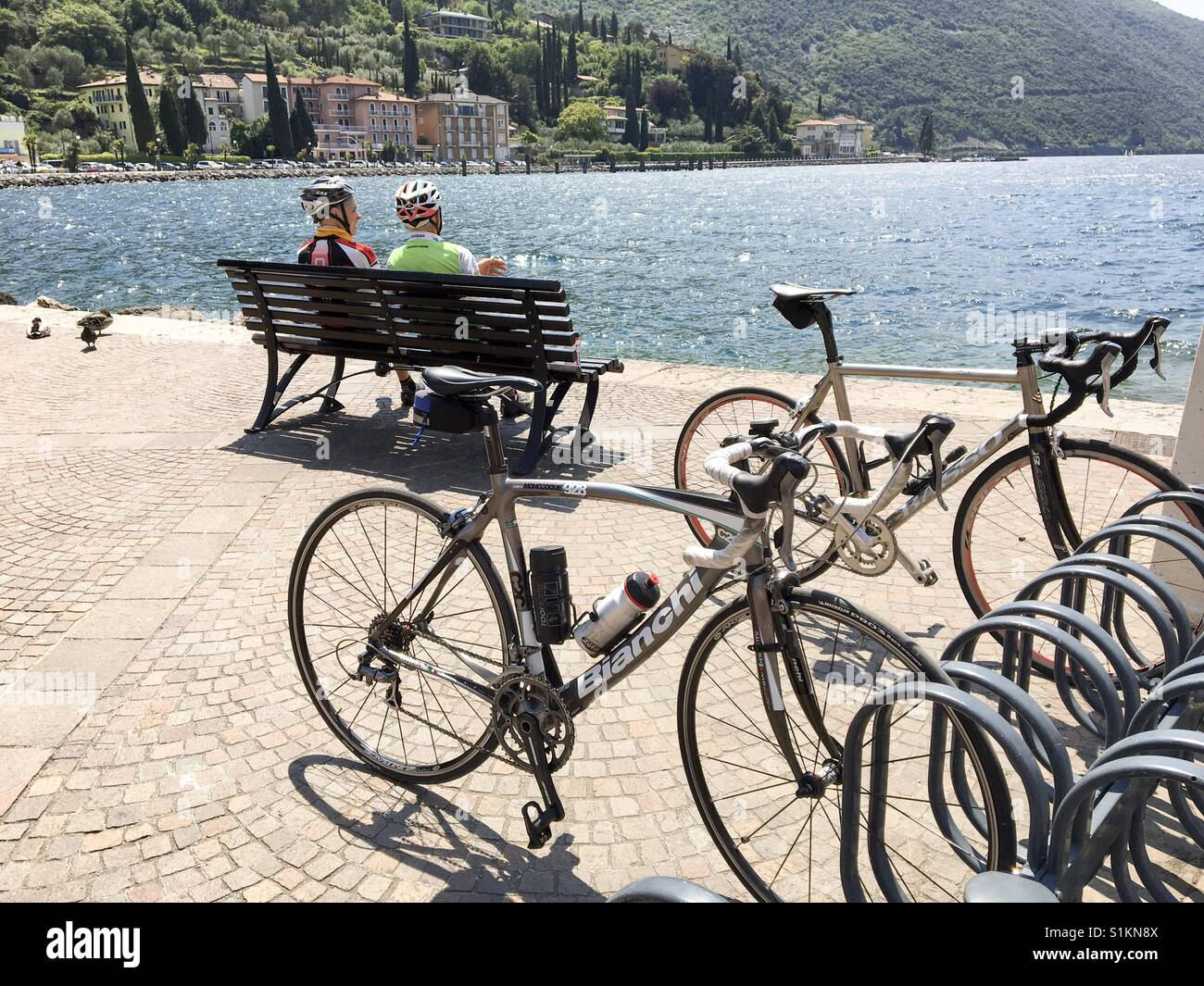 Torbole, Lake Garda, Italy- May 2017: Two cyclists take a well earned rest from their journey leaving their bikes - Stock Image