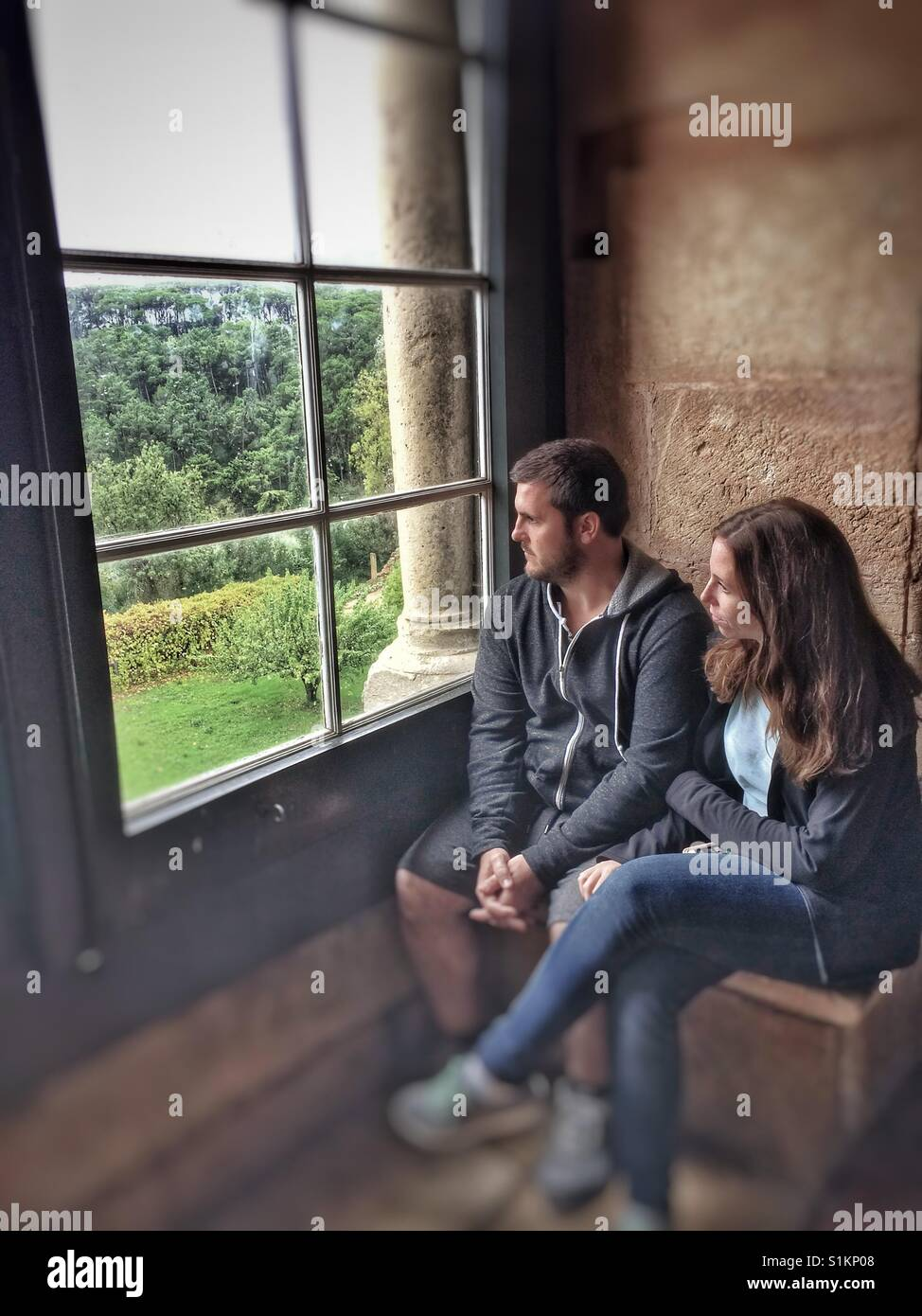 Couple looking out of window from a castle in Portugal. - Stock Image