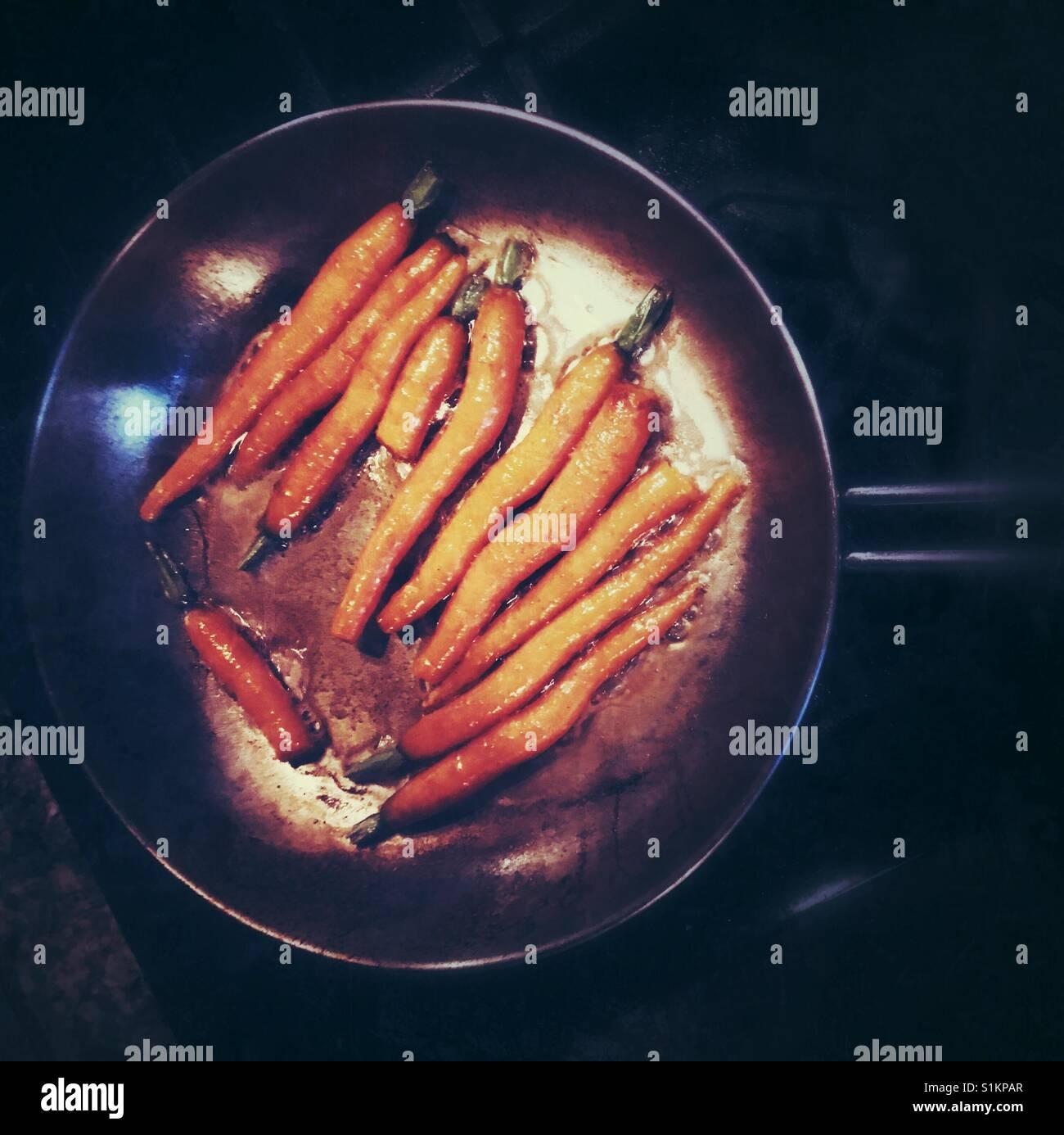 Seasonal fresh carrots simmering in butter in a pan. - Stock Image