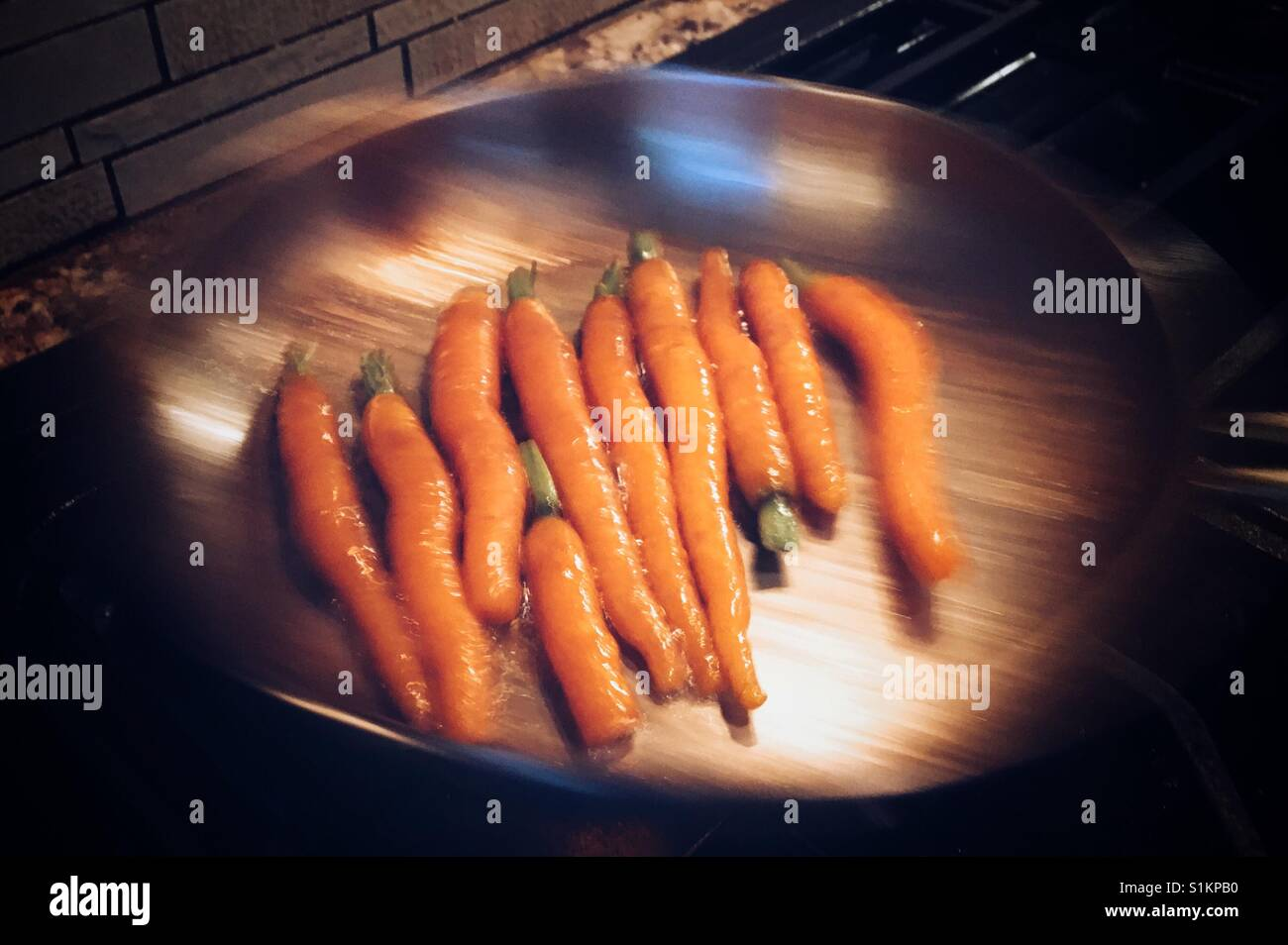 Farm fresh seasonal carrots simmering in butter being tossed in frying pan. - Stock Image