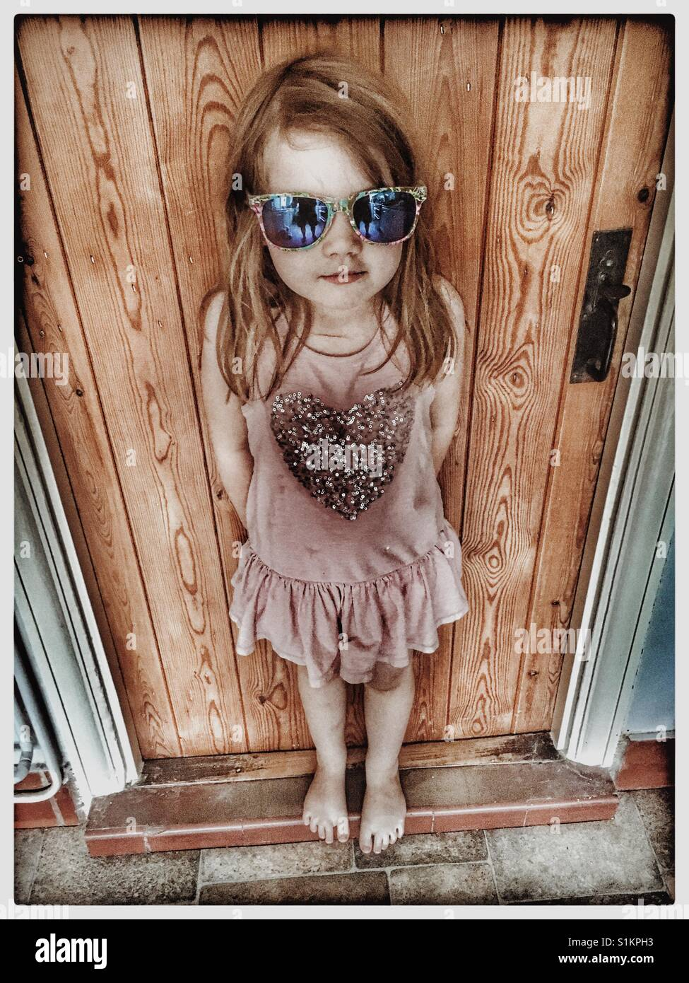 Red haired 5 year old girl in sunglasses. - Stock Image
