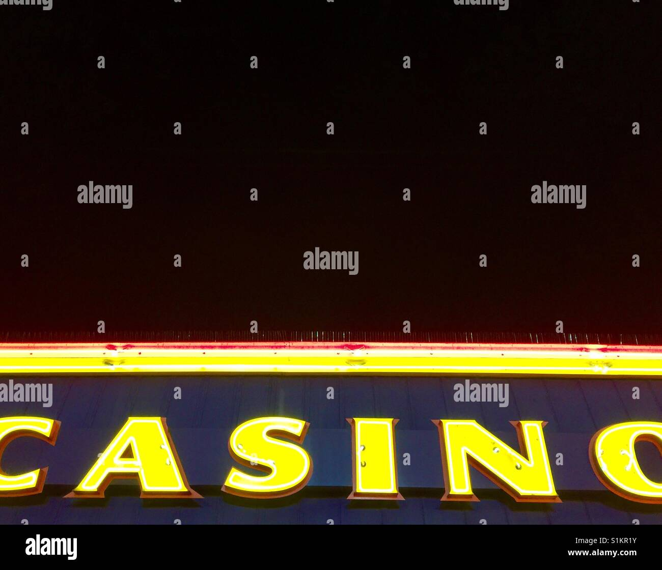 Illuminated casino sign at night against a black sky - Stock Image