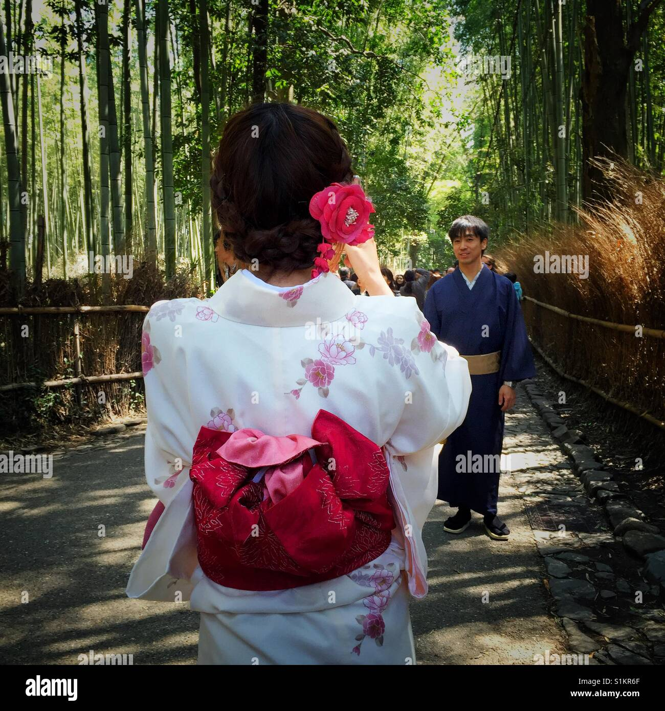 Clad in traditional kimono young Japanese woman taking picture of her boyfriend in bamboo garden in Kyoto - Stock Image