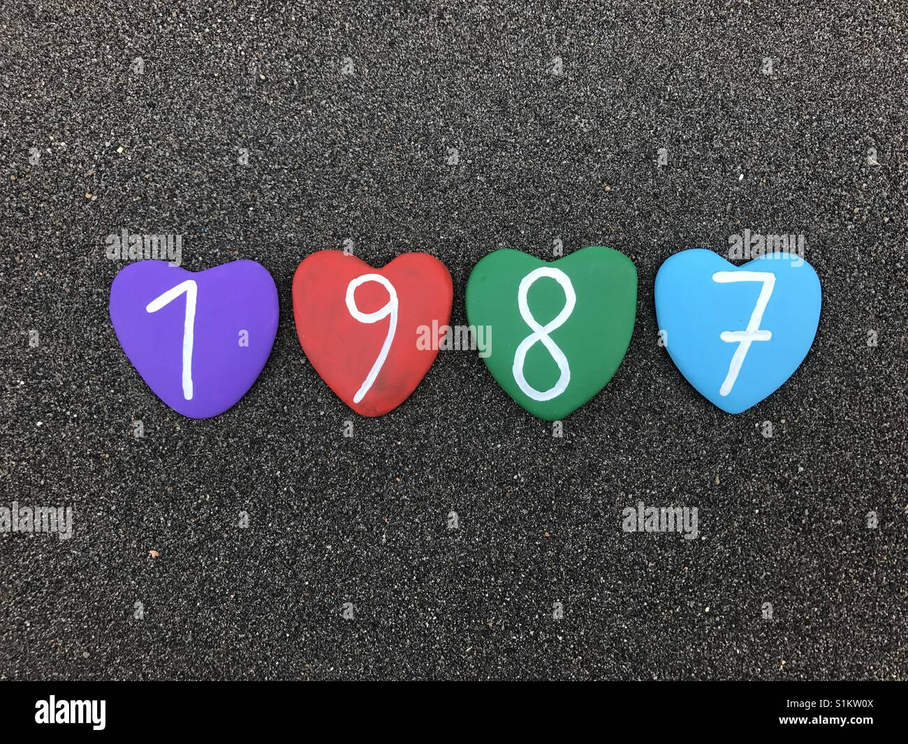 1988 year with colored heart stones over black volcanic sand - Stock Image