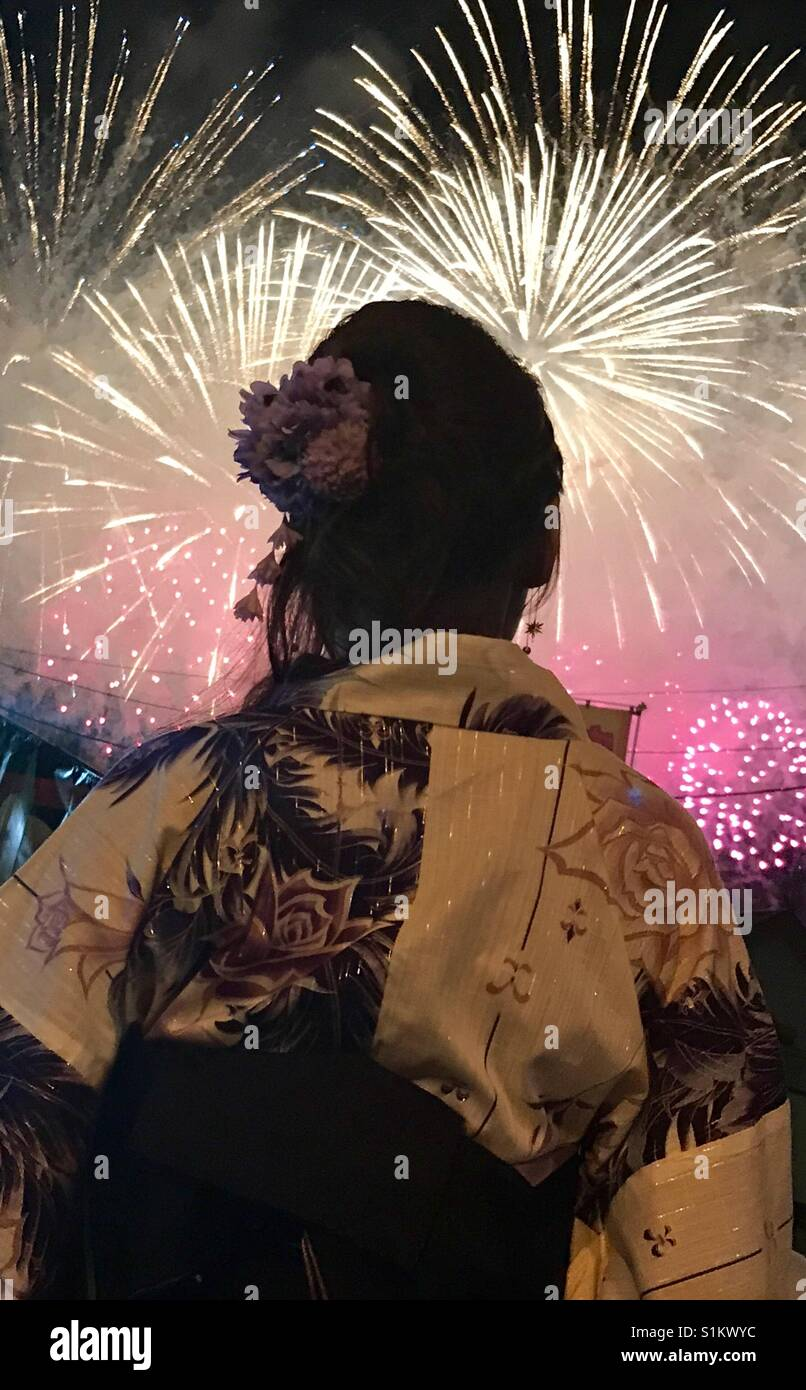 Japanese lady watching fire works. - Stock Image