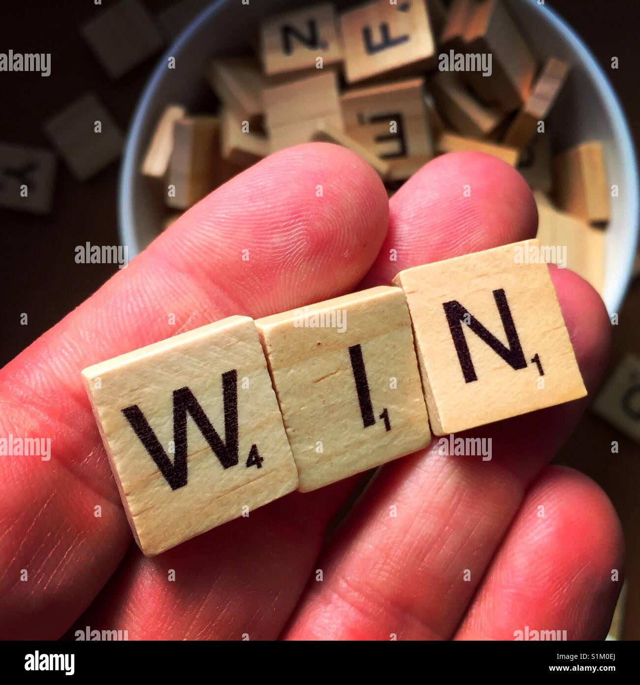 A close up shot of a man's hand holding wooden letters spelling win with other wooden letters in the background - Stock Image