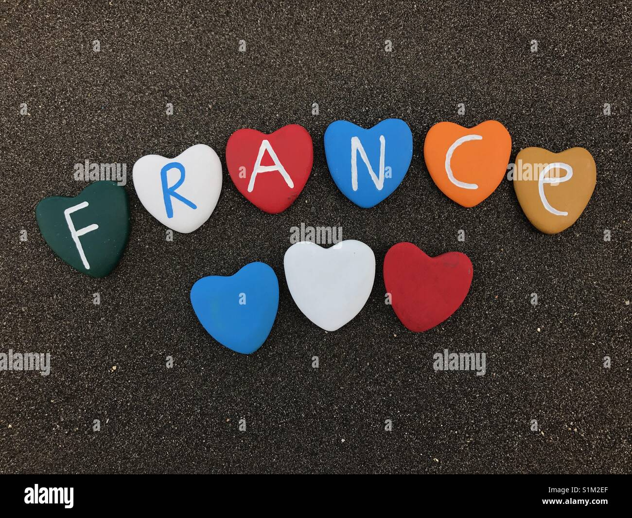 France, country name with painted heart stones over black volcanic sand Stock Photo