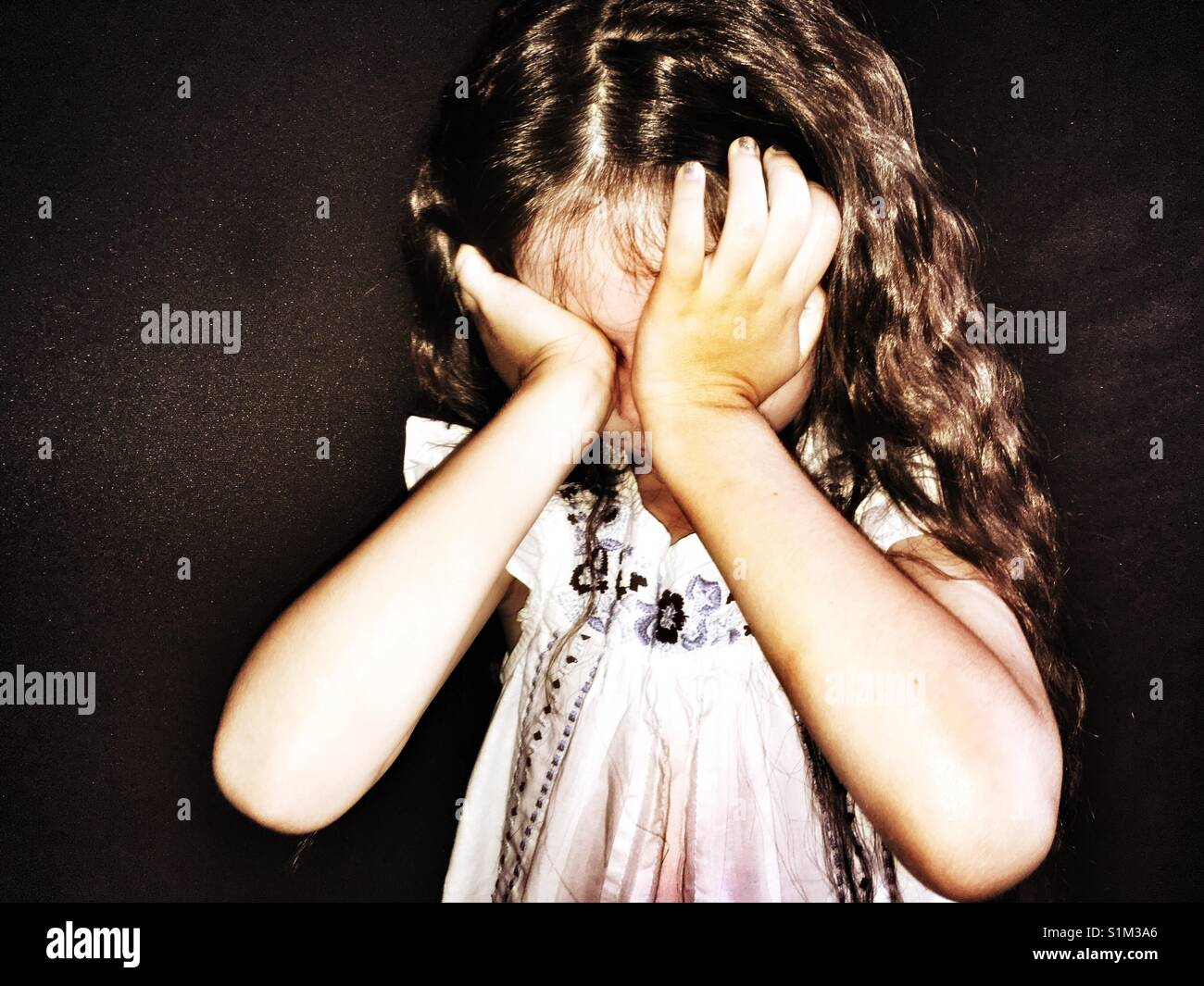 Upset child wiping tears away from her eyes - Stock Image