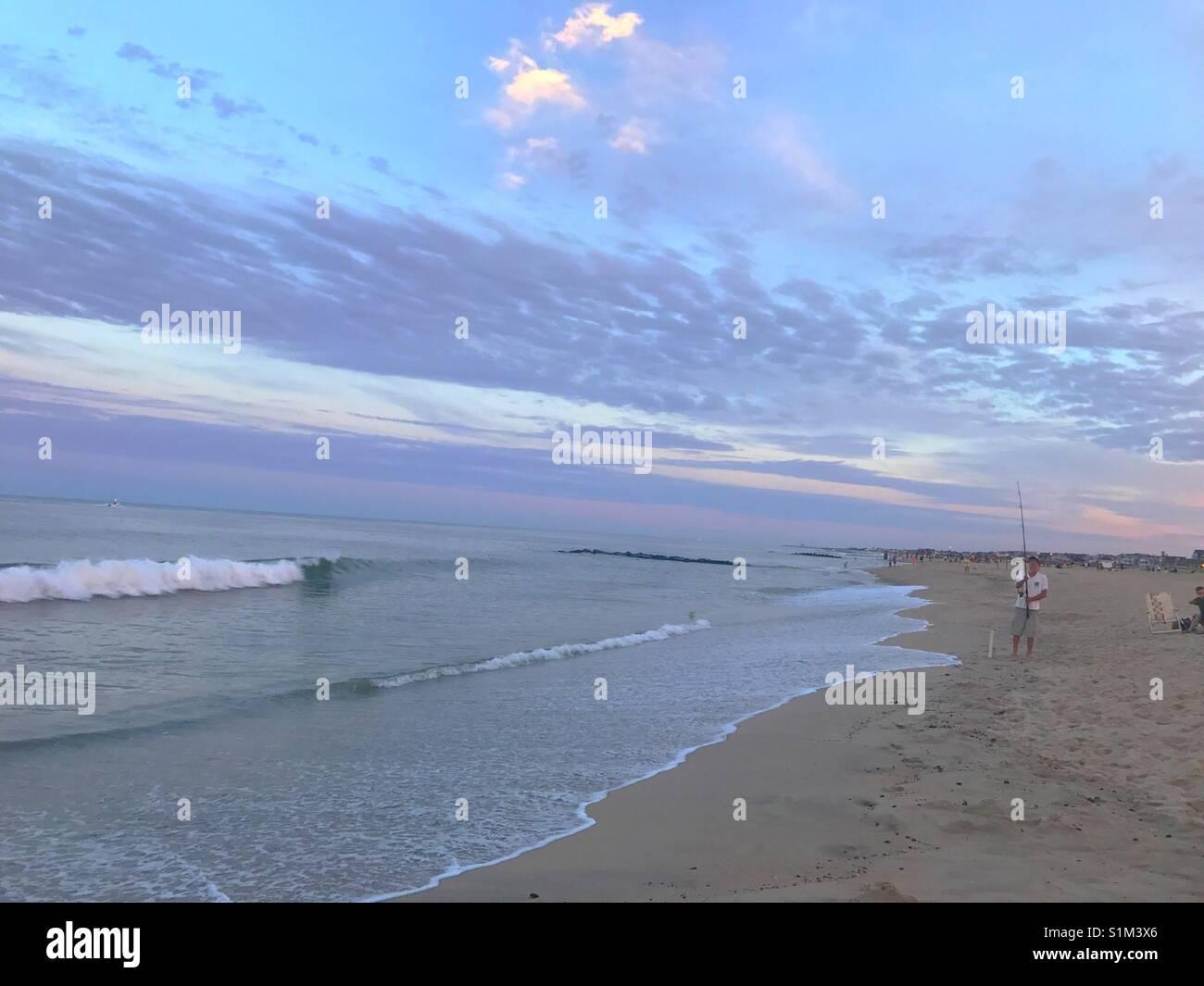 Purple sky green ocean and fishermen at Ocean Grove beach