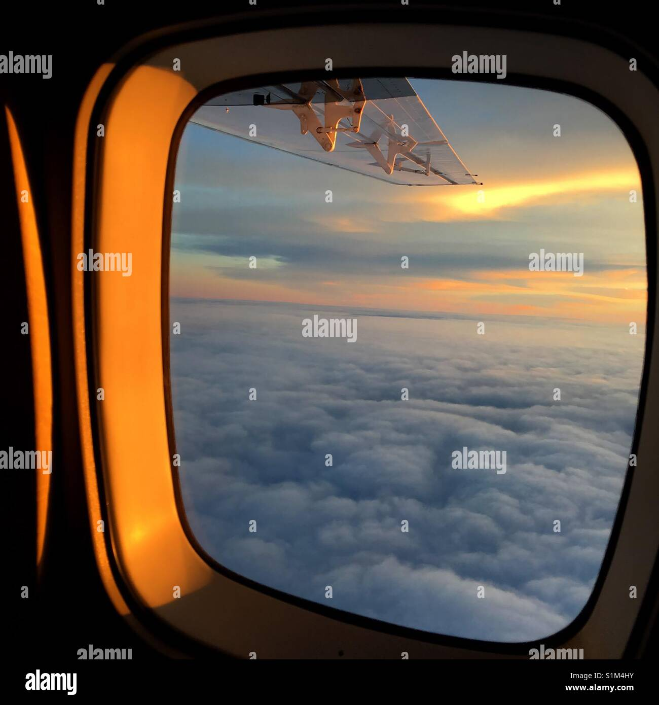 Sunrise  above the clouds on a small commuter plane - Stock Image