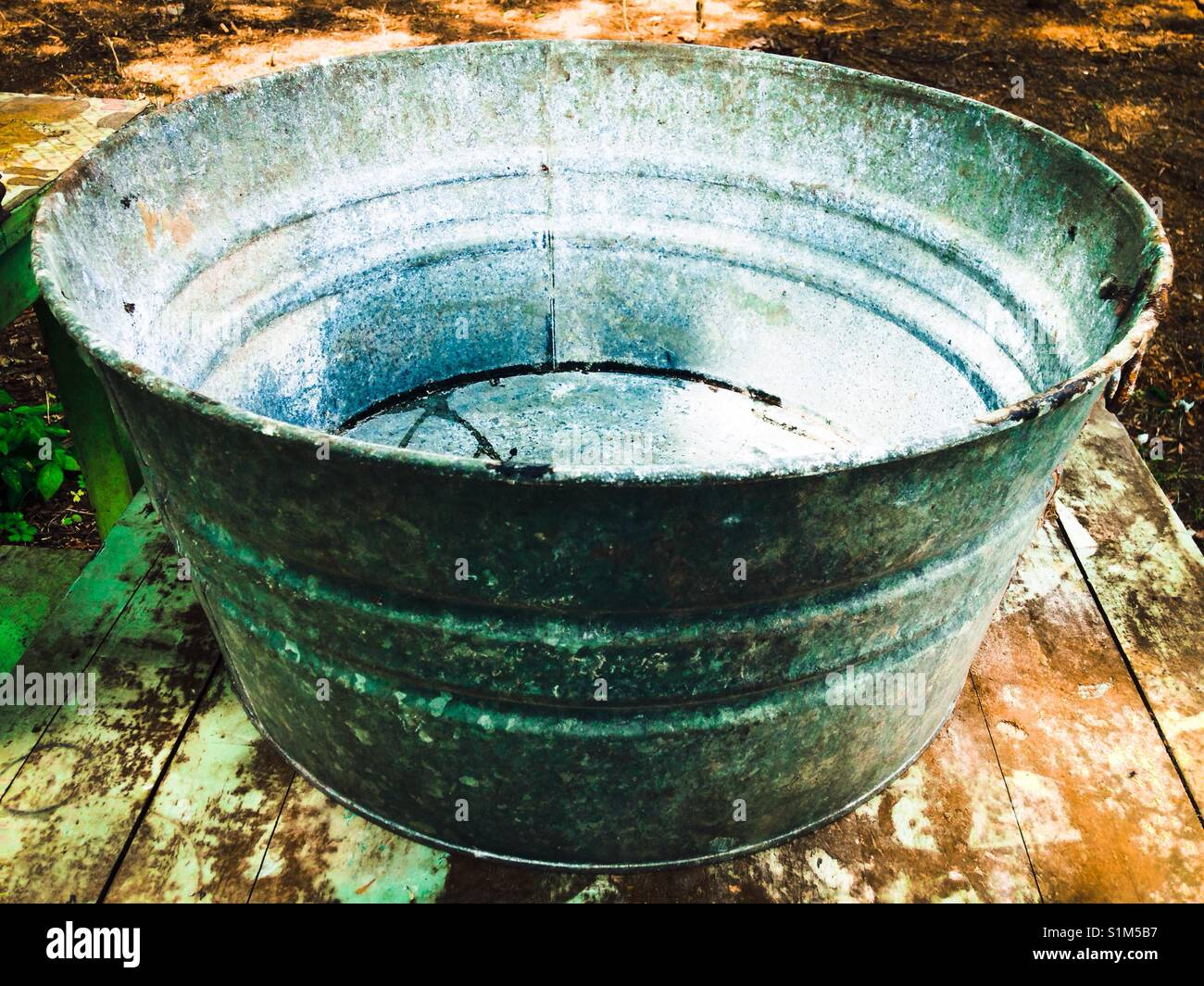 Old washtub found in basement sitting on old table - Stock Image