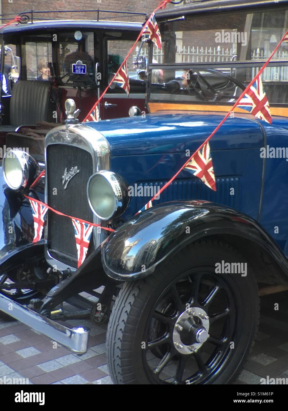 Antique Austin car at Costermongers annual festival decorated with bunting of British flag in London - Stock Image