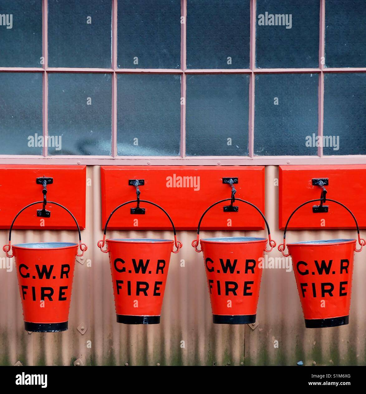 Traditional fire buckets from the Great Western Railway hang on the side of a platform building at the Kidderminster - Stock Image