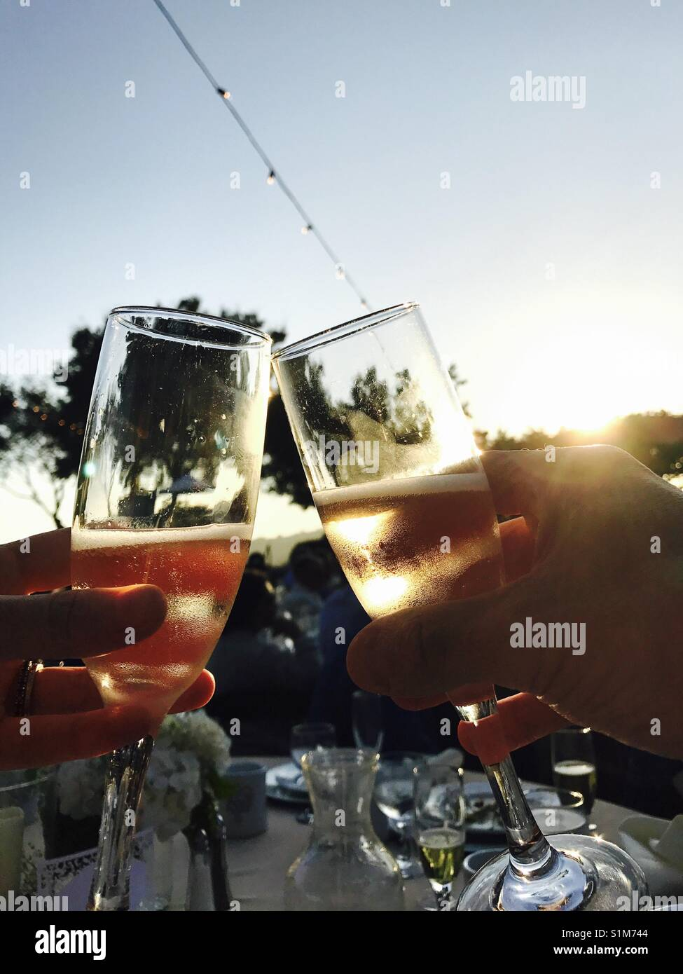 Two glasses of champagne toasting at a wedding at sunset. - Stock Image