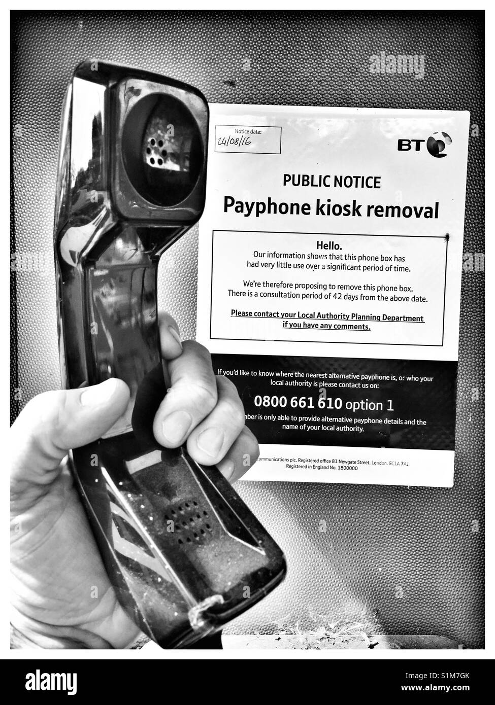 Vintage British Telecom (BT) Pay Phone kiosk handset with Removal Imminent Notice. - Stock Image