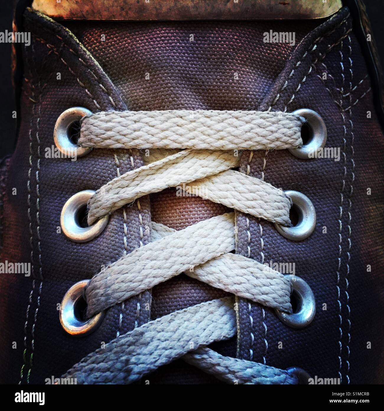 A close up shot of an old worn out canvas shoe - Stock Image