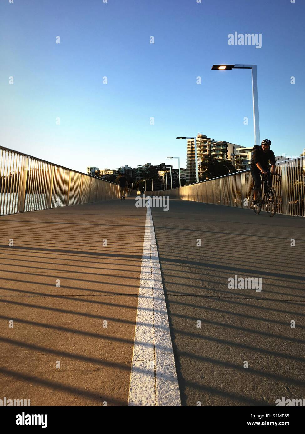Low-angle view of pedestrians and cyclist along Brisbane Riverwalk during late afternoon - Stock Image