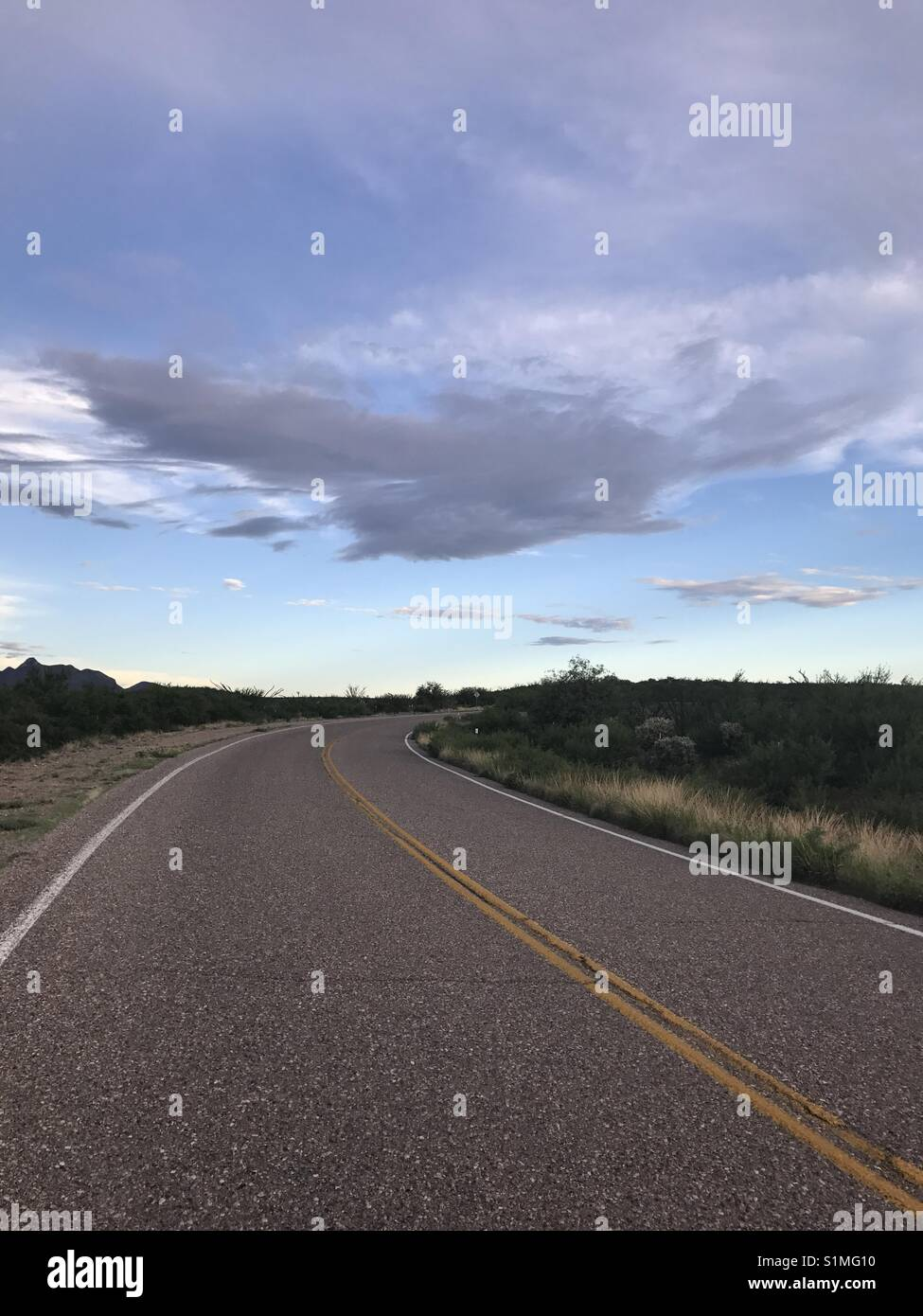 Road leading into the distance with beautiful clouds - Stock Image