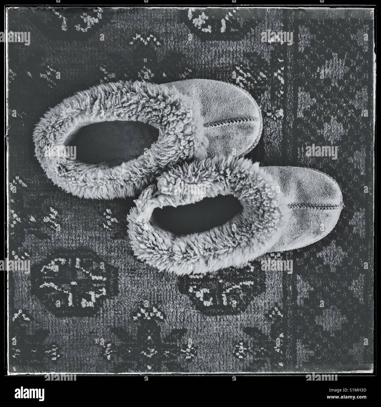 Black and white photo of wool slippers on carpet. - Stock Image