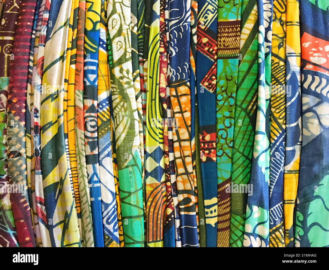Bale of brightly coloured cotton fabric - Stock Image
