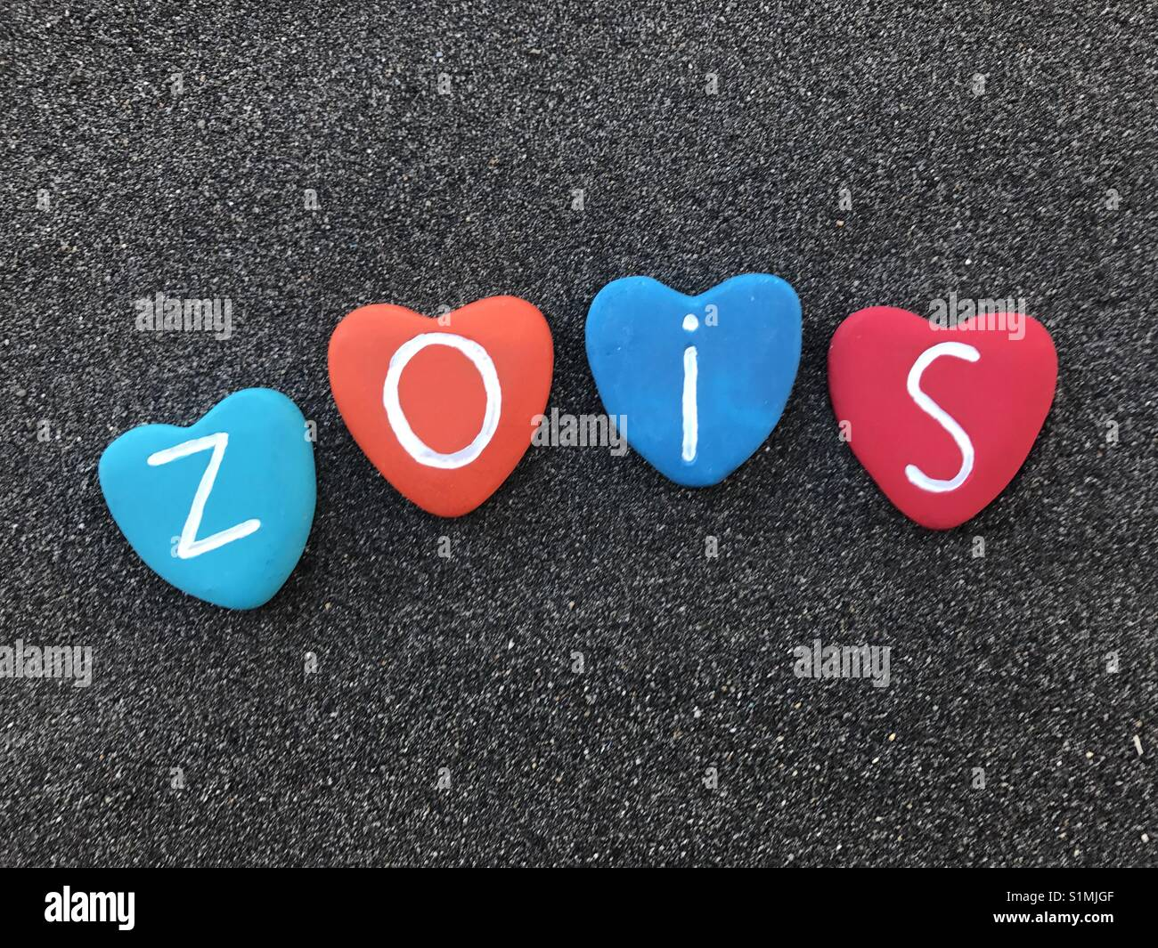 Zois, greek origin masculine name with colored heart stones over black volcanic sand - Stock Image