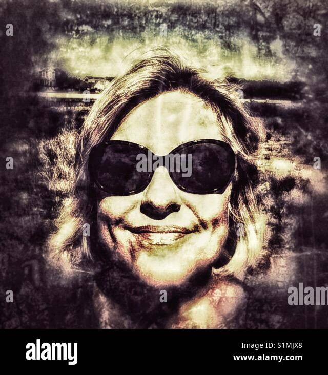 A woman with sunglasses on the beach; grunge, grainy photo - Stock Image