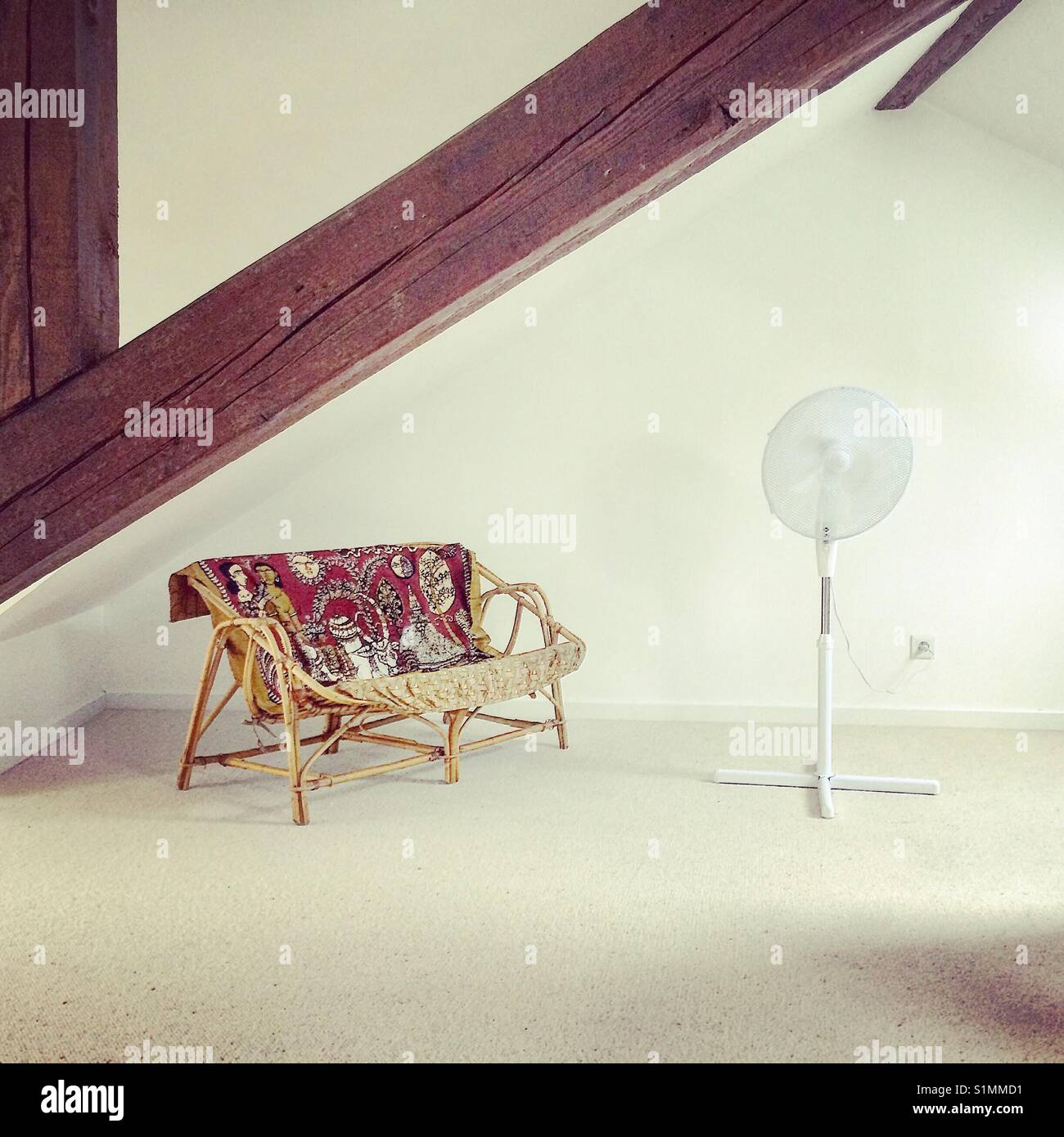 Seat and fan in attic room - Stock Image