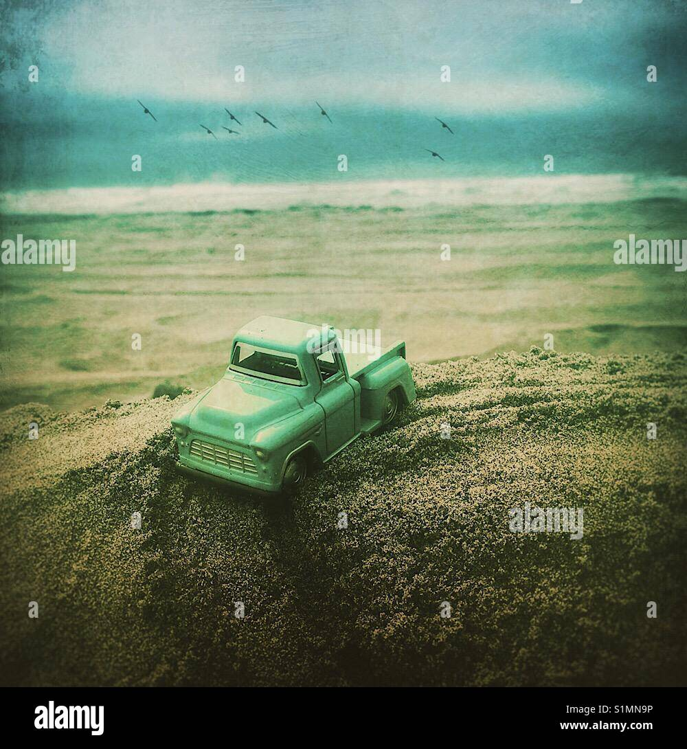 Toy pickup truck at the beach - Stock Image