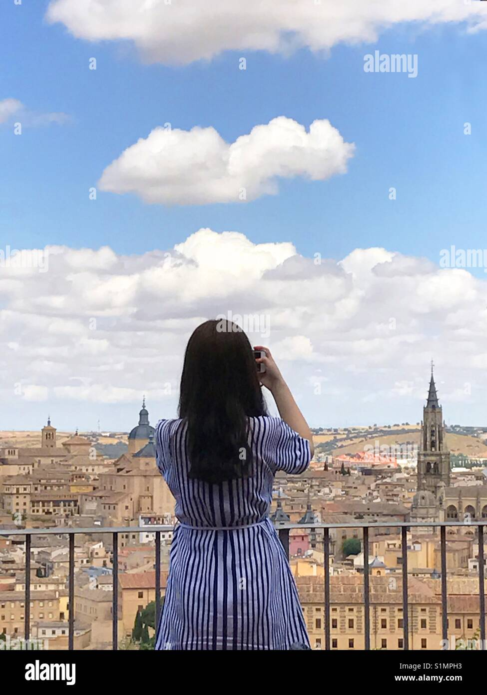 Woman taking photos at the viewpoint over the city. Toledo. Spain. - Stock Image
