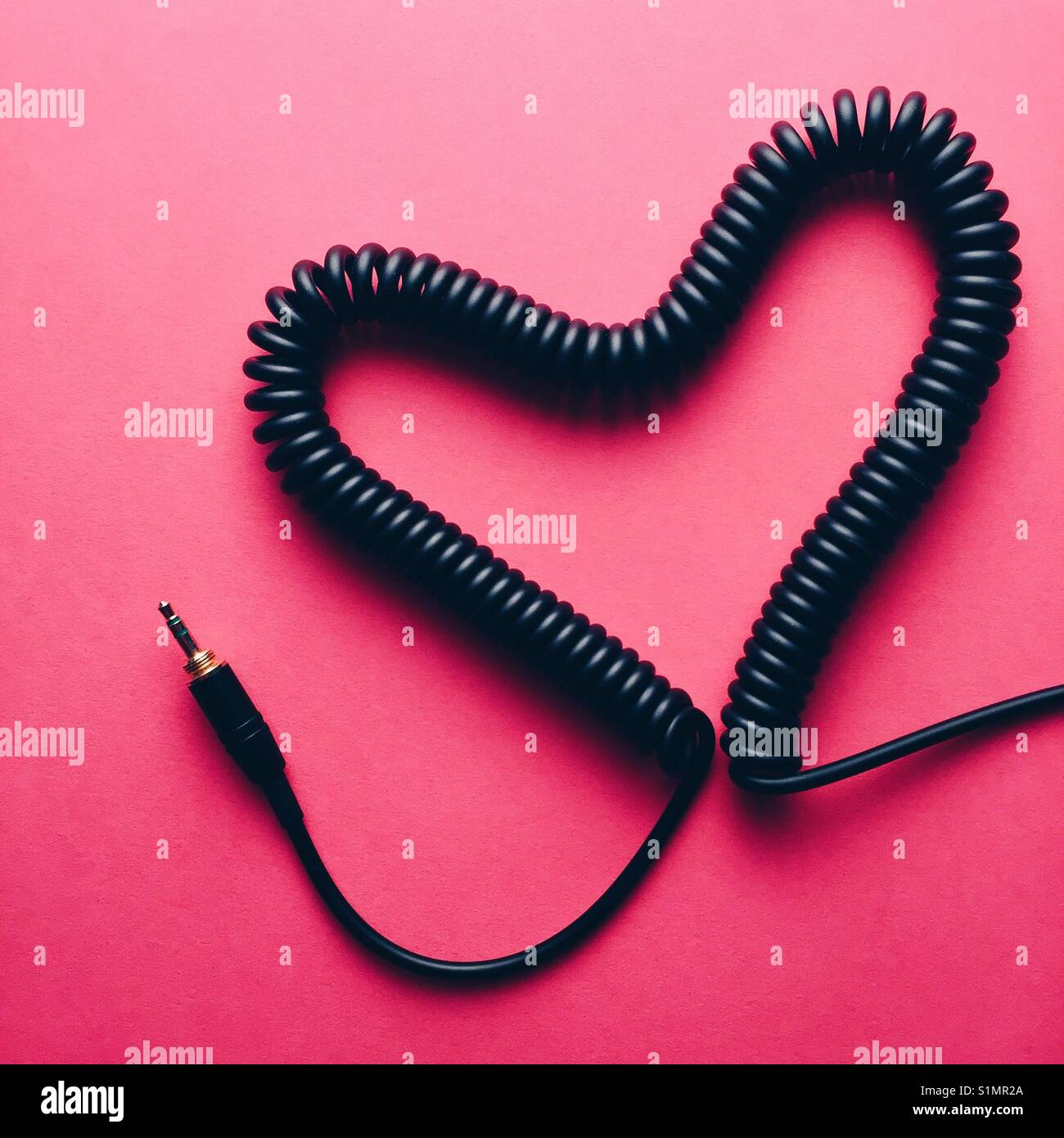 A coiled headphone cable made into a heart shape on a pink background - Stock Image