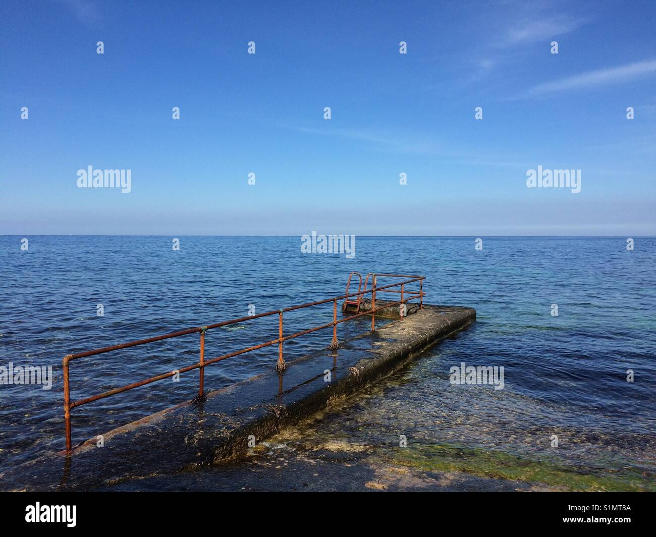 Old pier into the endless ocean - Stock Image