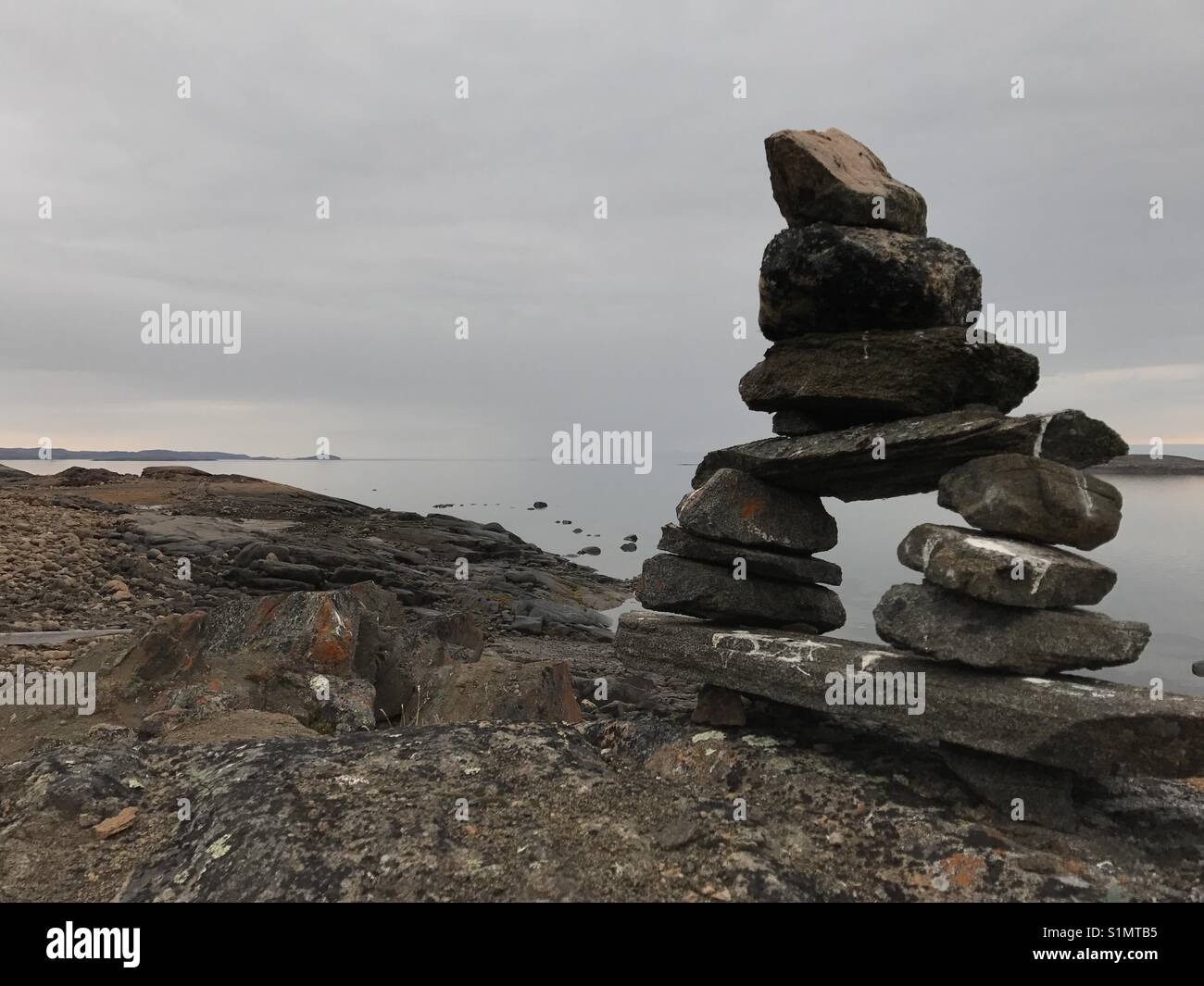 Inukshuk on Arctic landscape near Iqaluit, Nunavut, Canada - Stock Image
