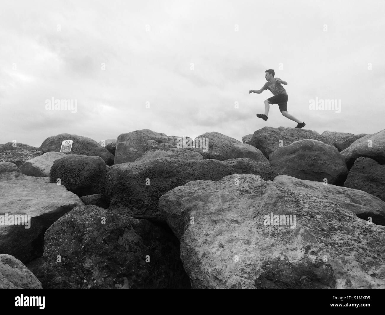 Boy leaping over boulders - Stock Image