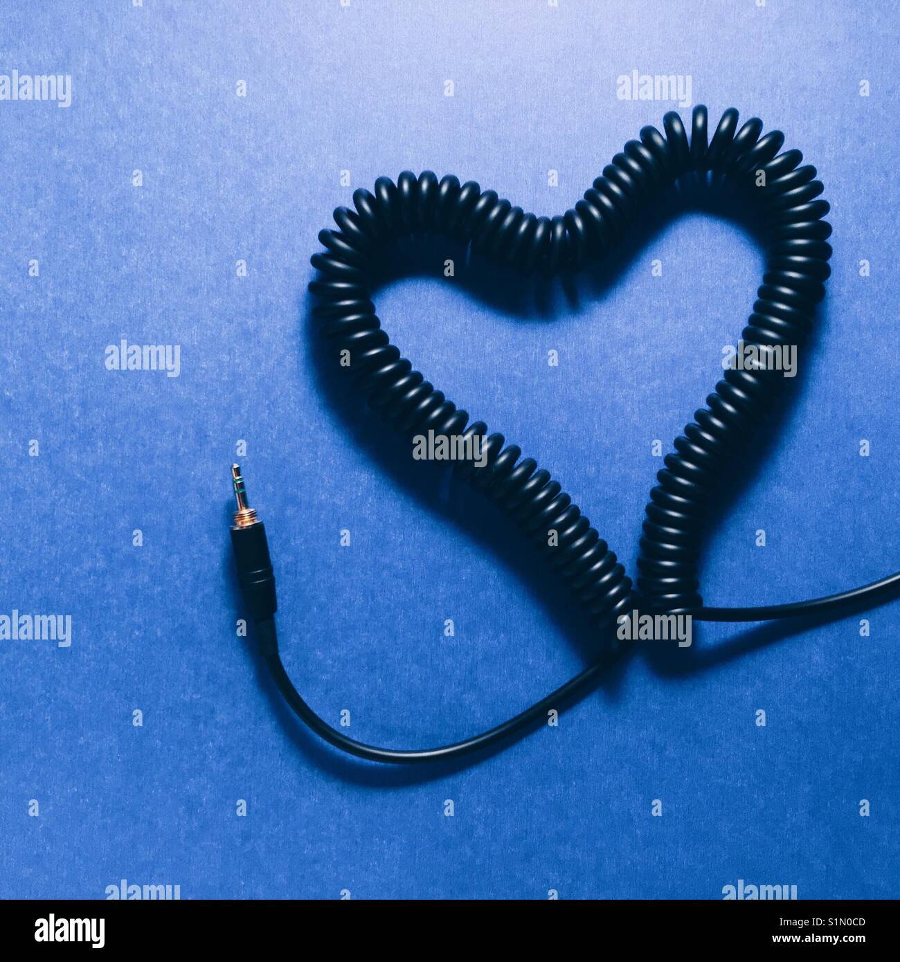A coiled headphone cable made into a heart shape on a blue background - Stock Image