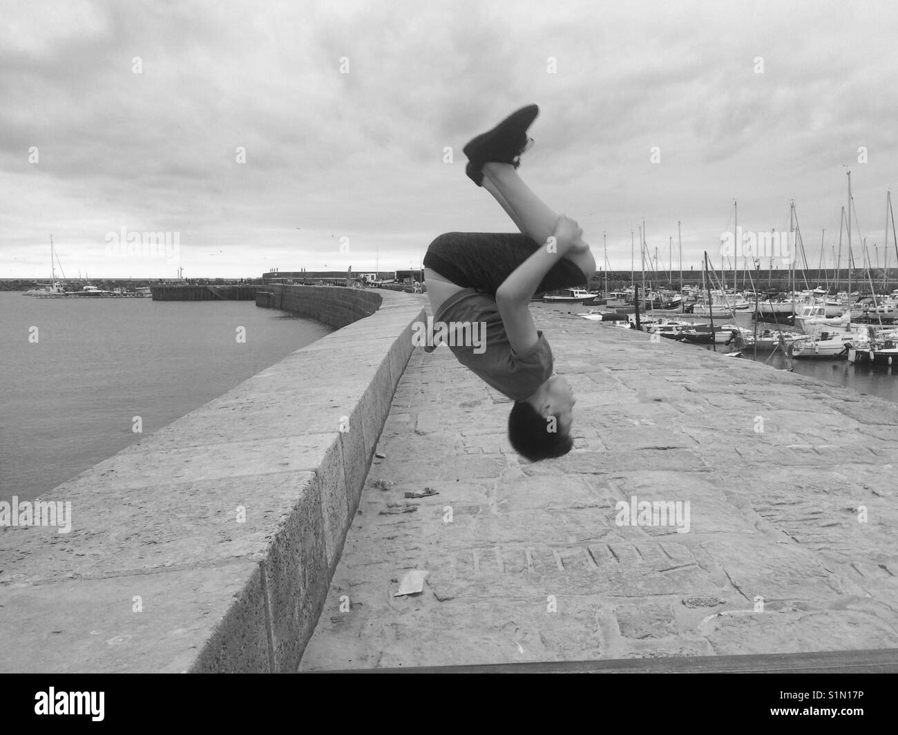 Boy somersaulting in the air - Stock Image