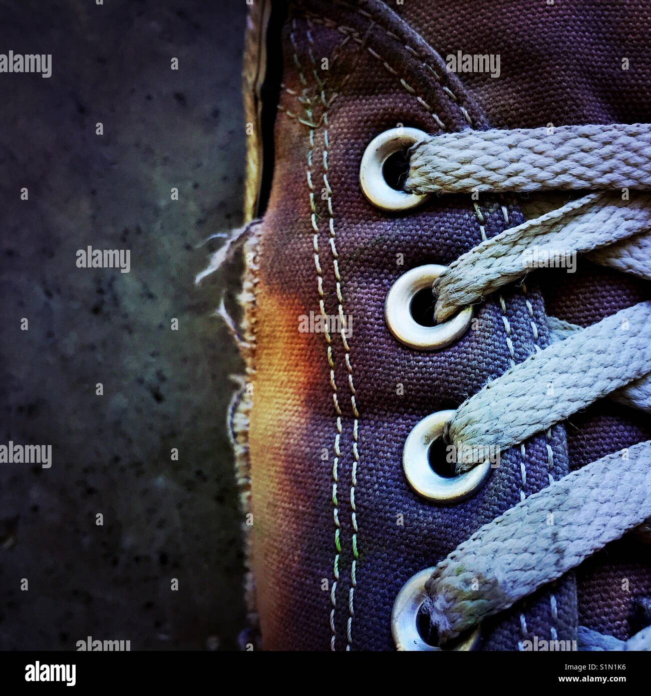 A close-up detail shot of an old worn out canvas shoe - Stock Image