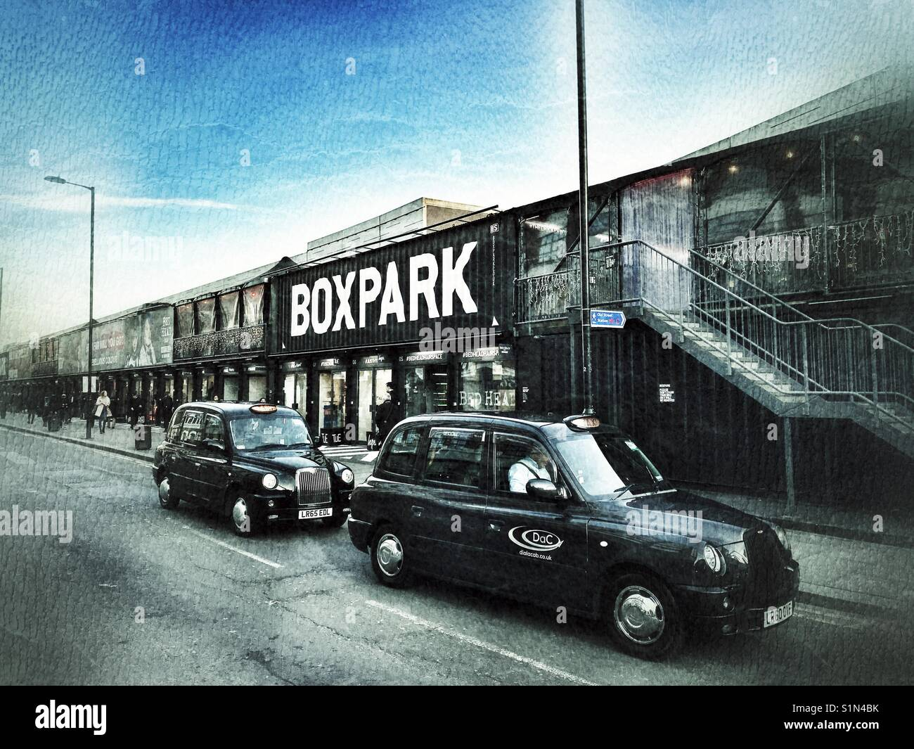Two London black cabs at Shoreditch Boxpark - Stock Image