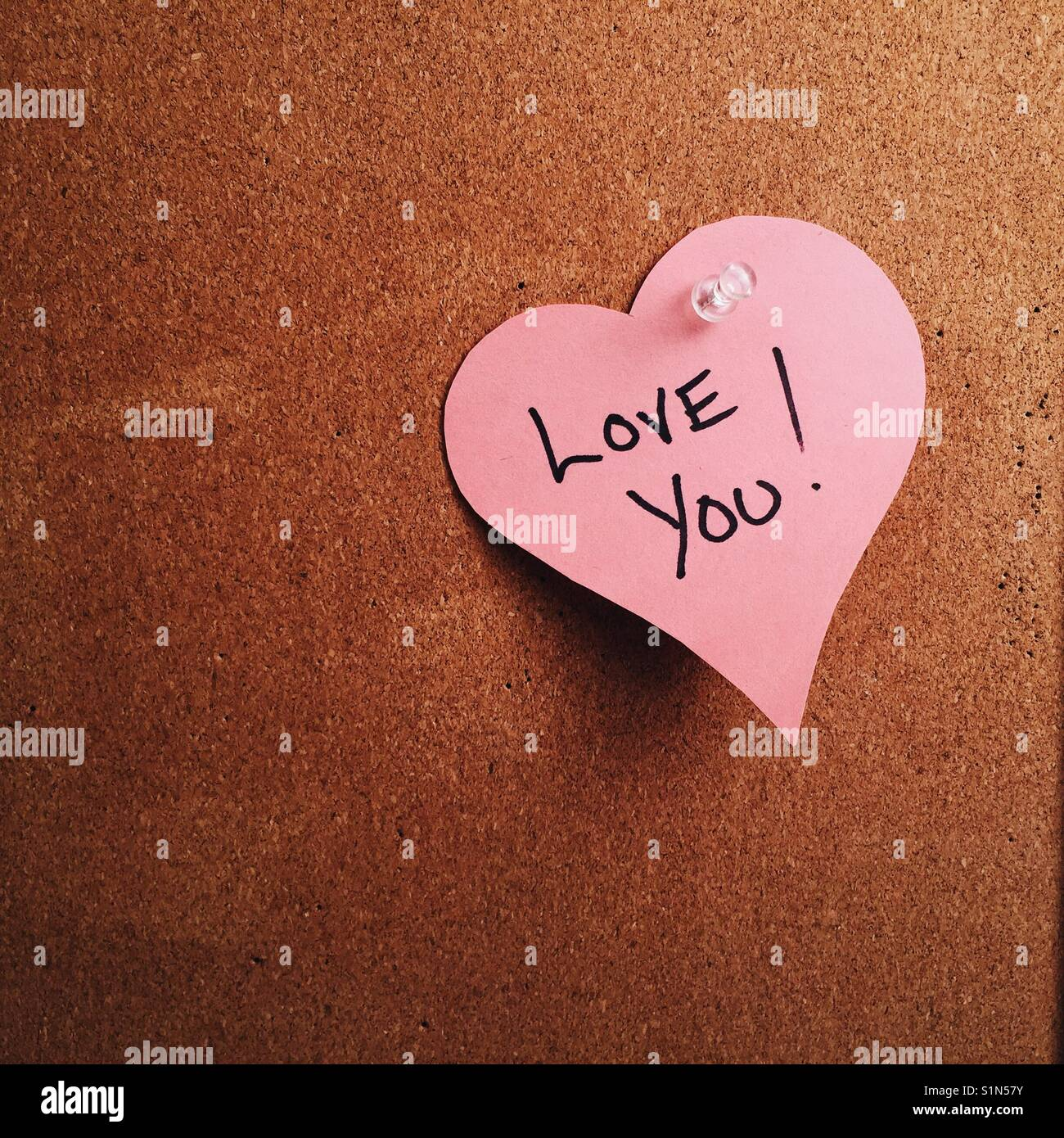 A Heart Shaped Note With The Words I Love You Written On It Pinned To A Cork Board