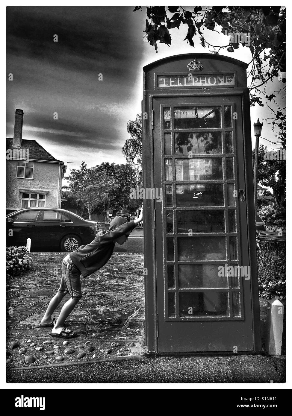 Boy supporting a leaning Telephone Box. - Stock Image