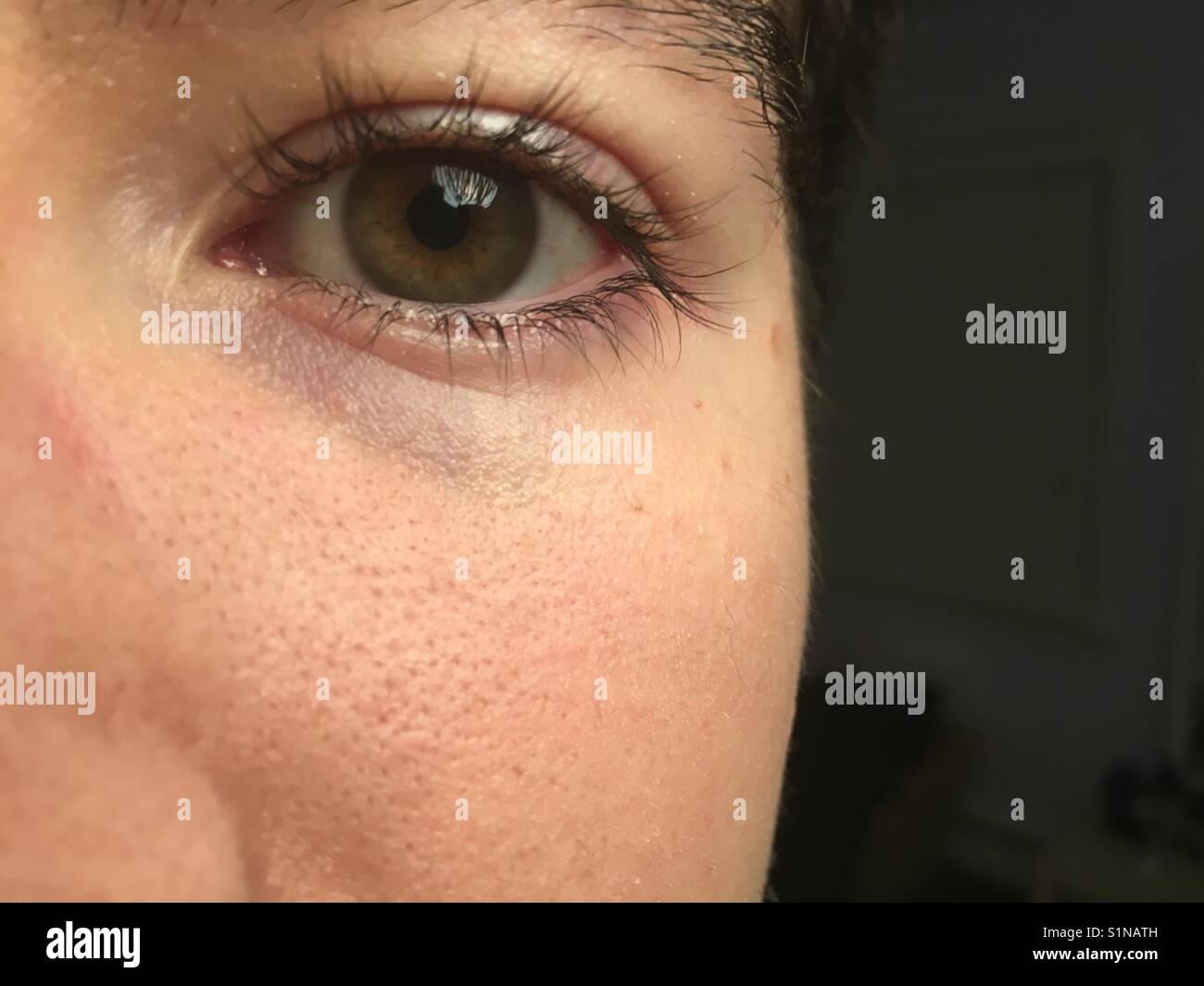 Half of man's face showing eye. - Stock Image