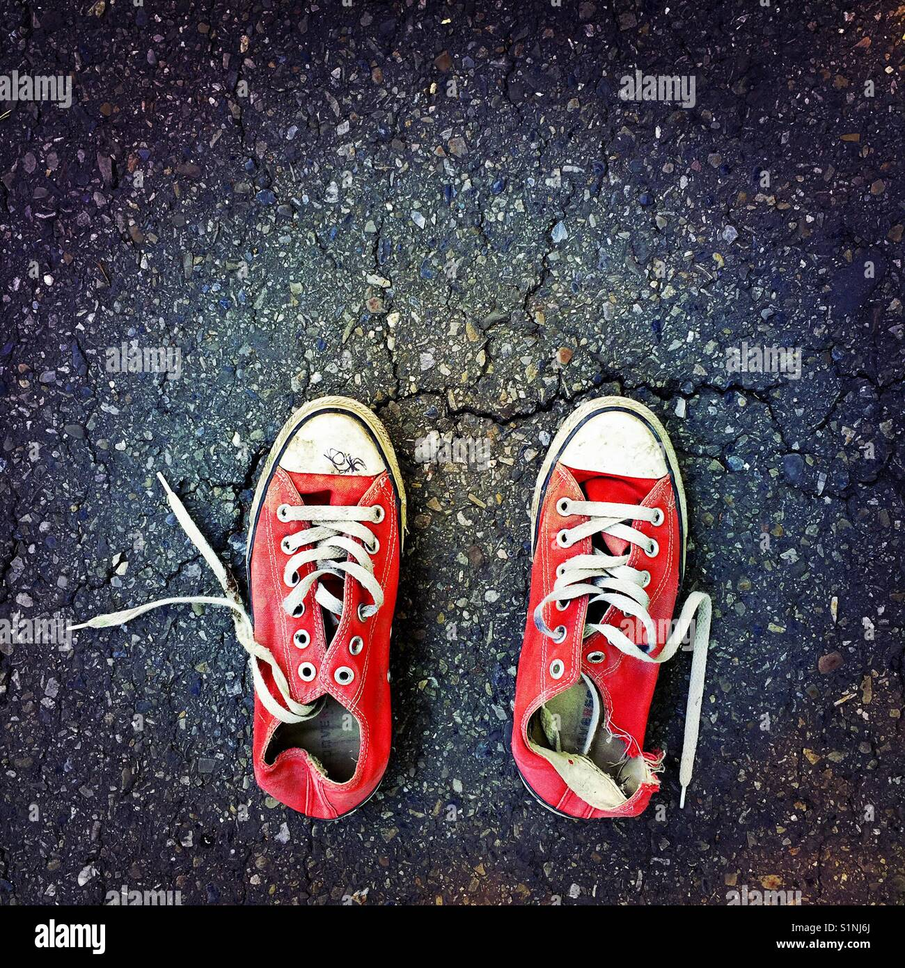 60bc4b3cdc73 An old worn out pair of red Converse sneakers on an asphalt surface ...