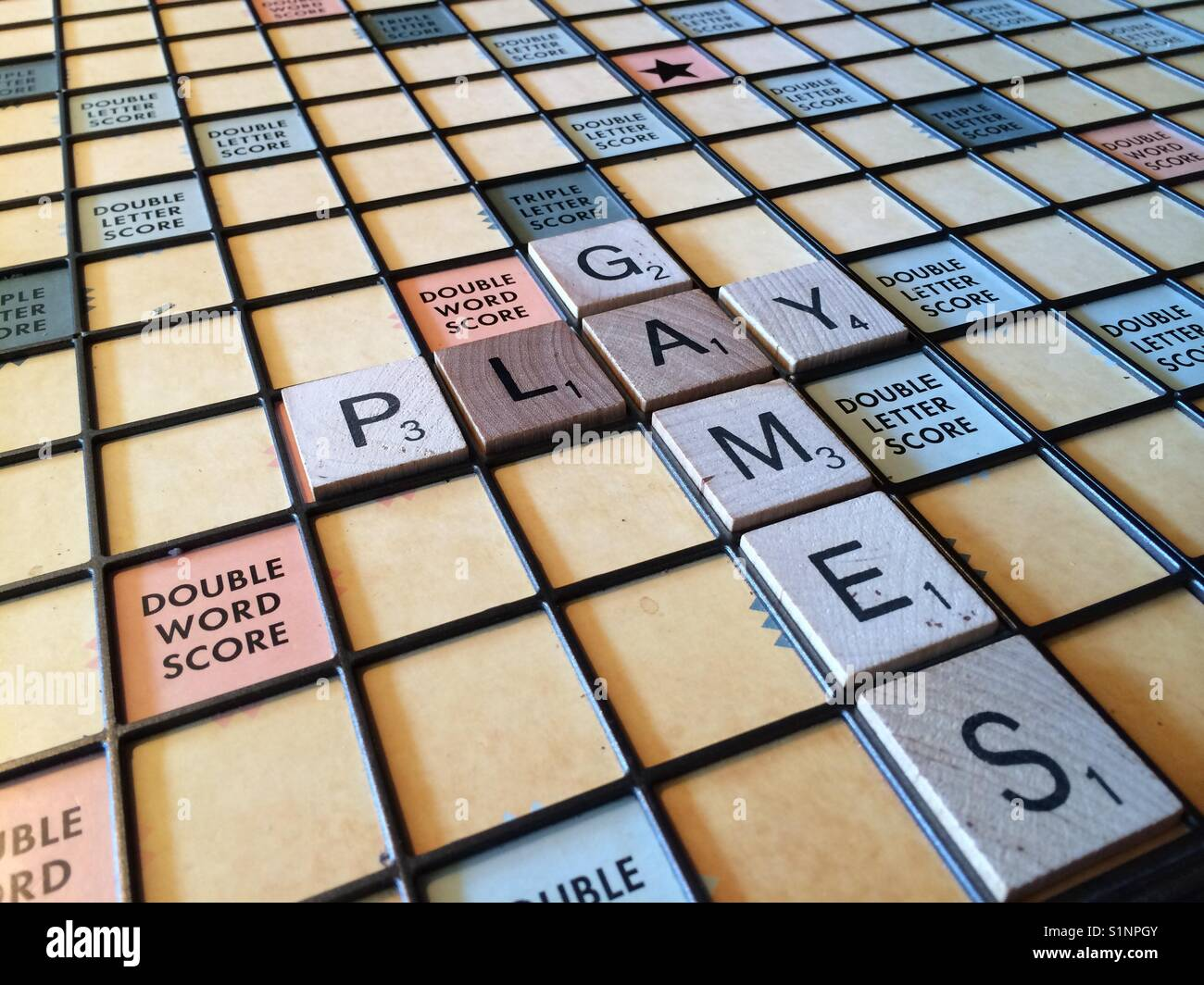 The words 'play games' on a Scrabble board - Stock Image