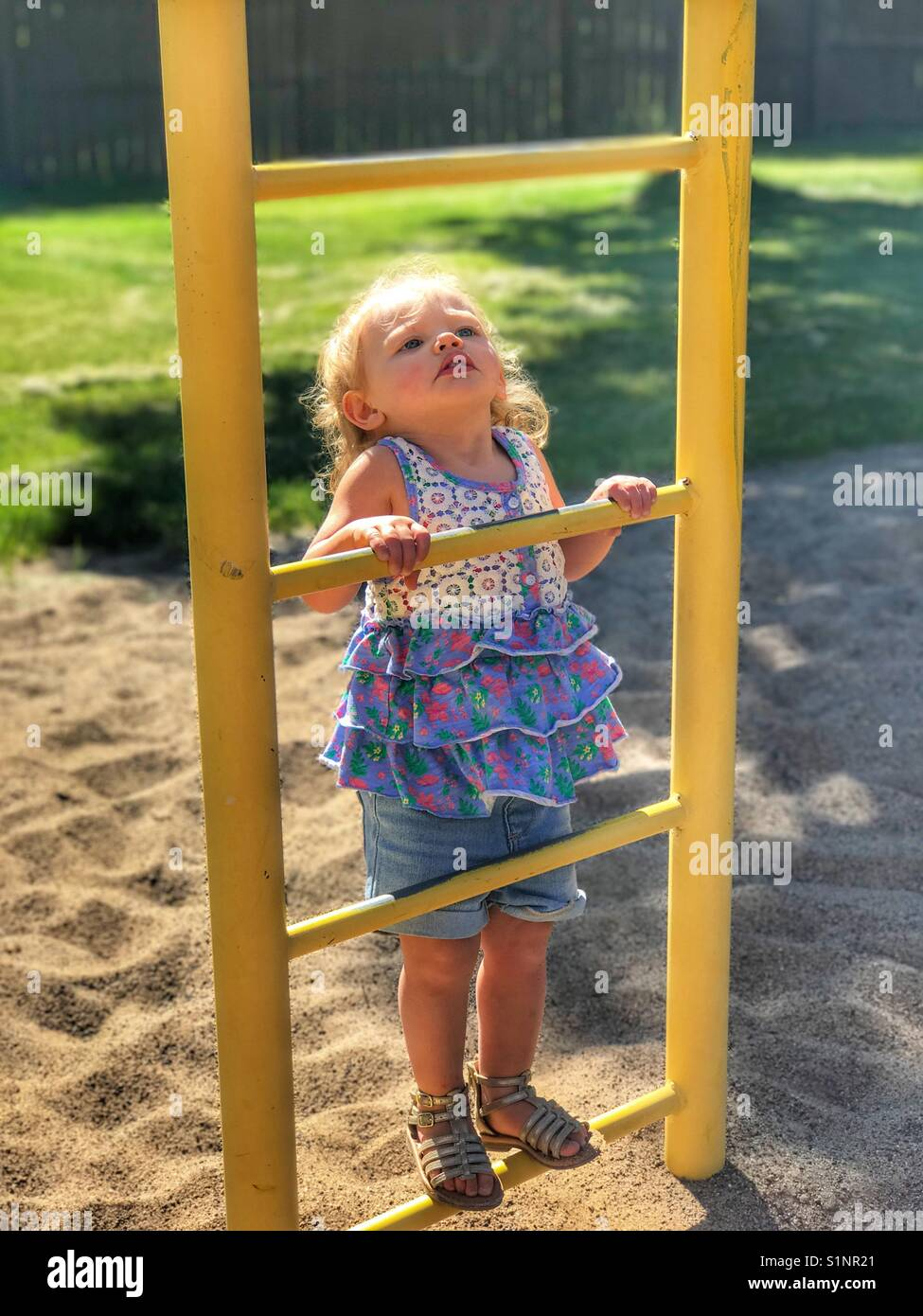 Baby climbing the ladder on the playground equipment while looking up - Stock Image