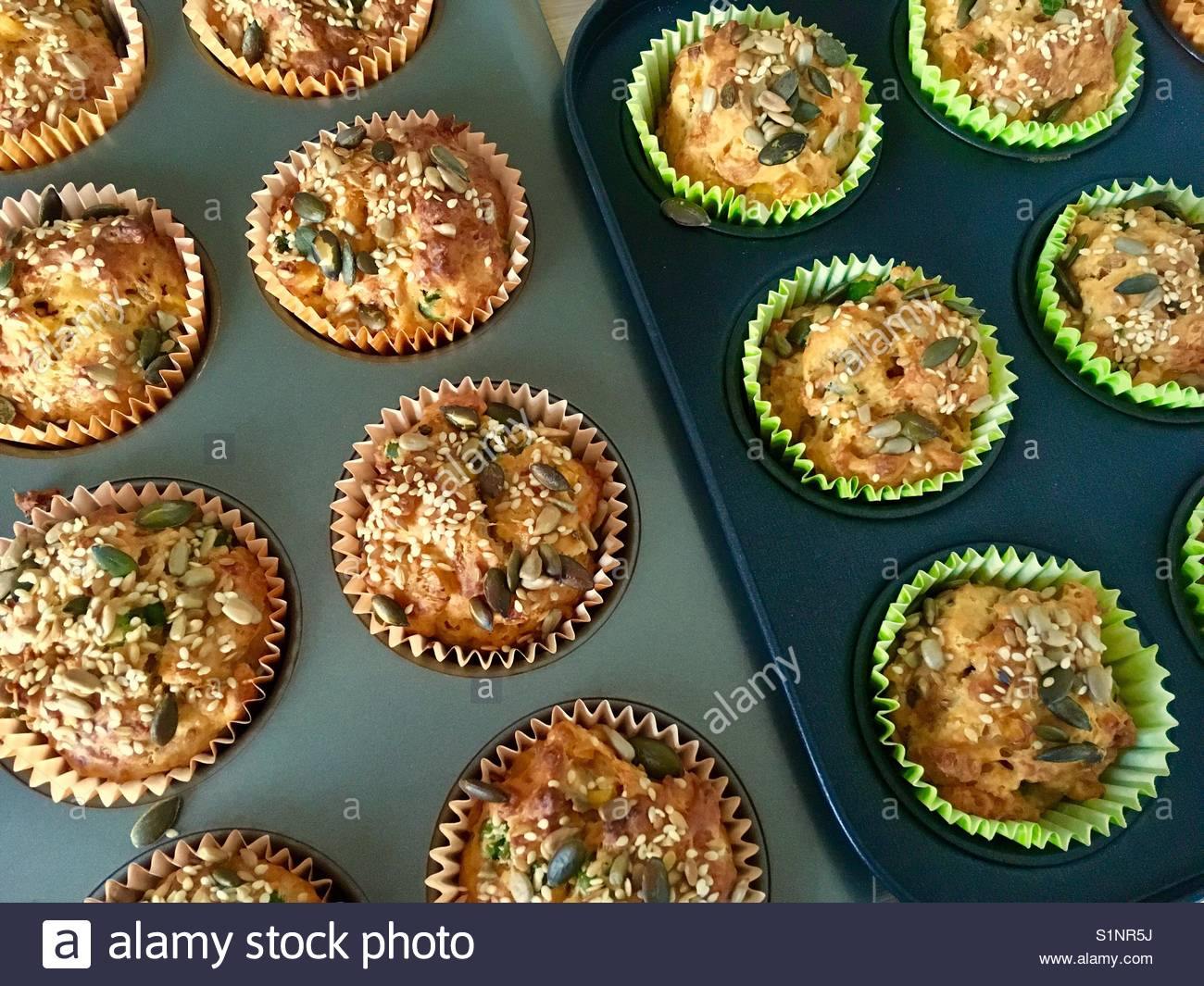 Home made savoury muffins topped with seeds - Stock Image