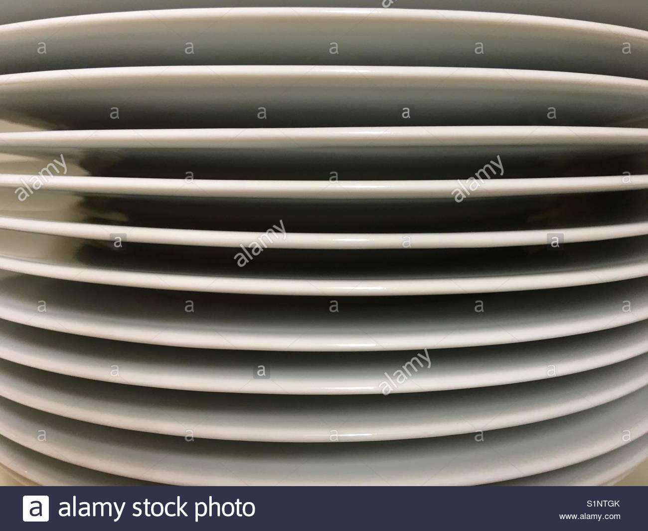 Stack of plain white plates viewed from the side - Stock Image