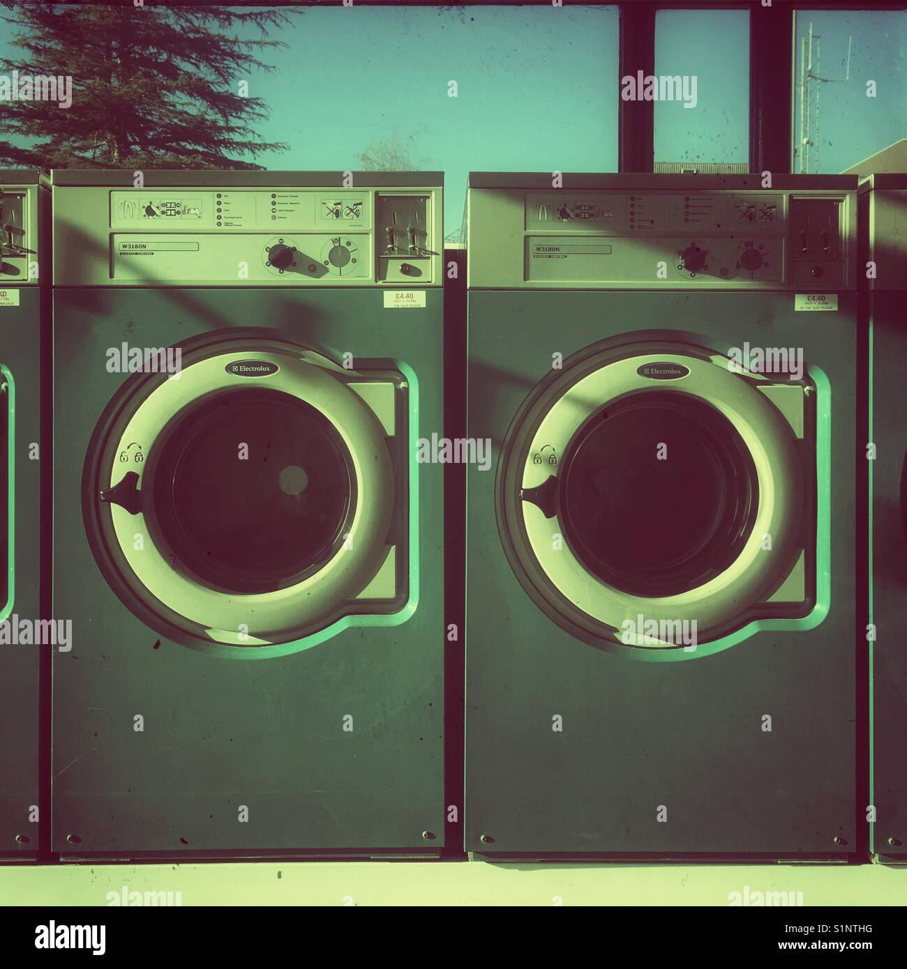 Coin operated washing machines at laundrette, UK - Stock Image