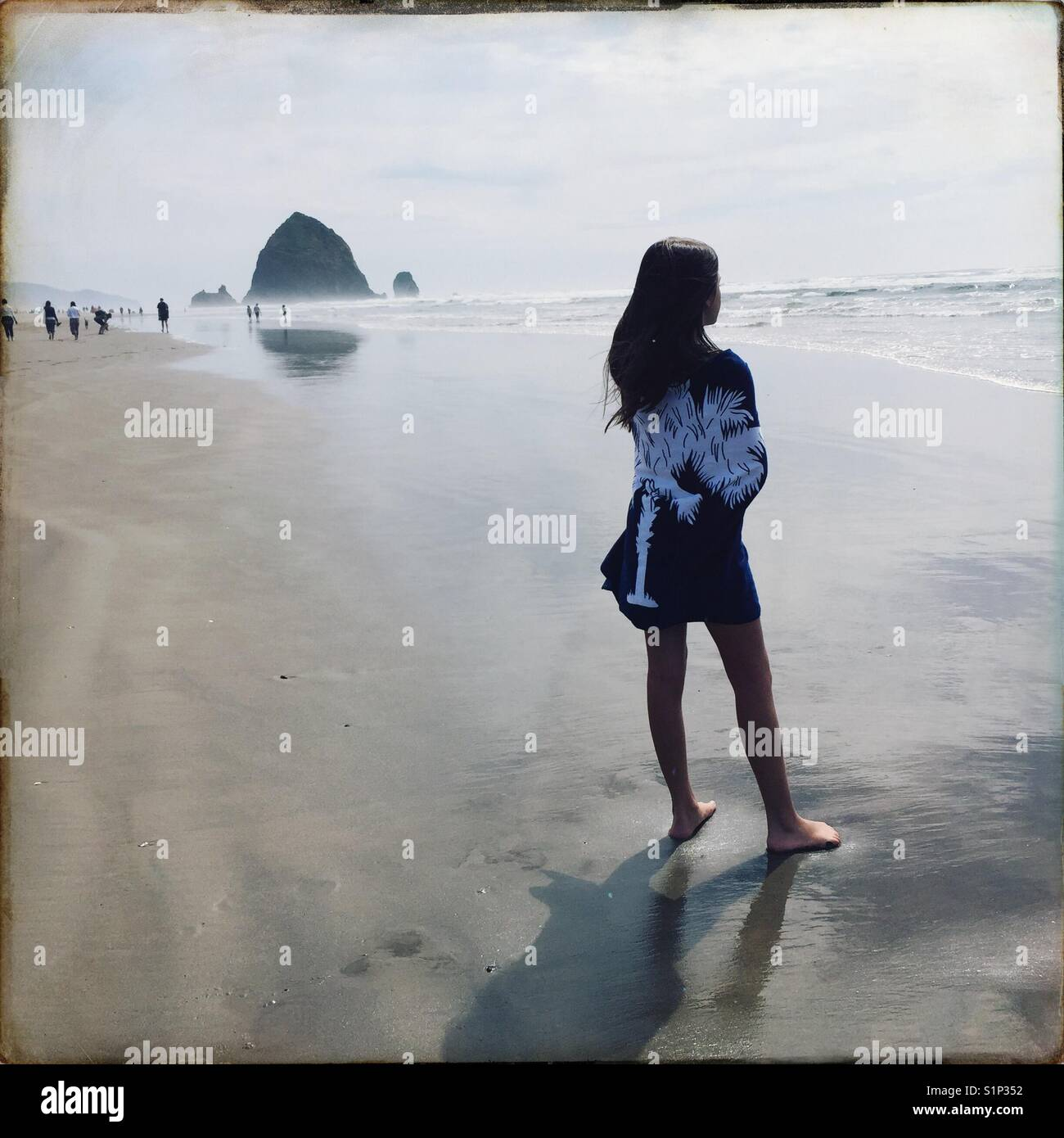 A child wrapped in a beach towel stands near the waters edge at cannon beach, Oregon on a summer day. - Stock Image