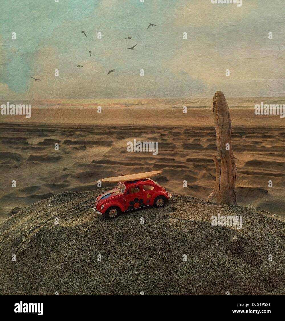 Toy car with surfboard at the beach - Stock Image