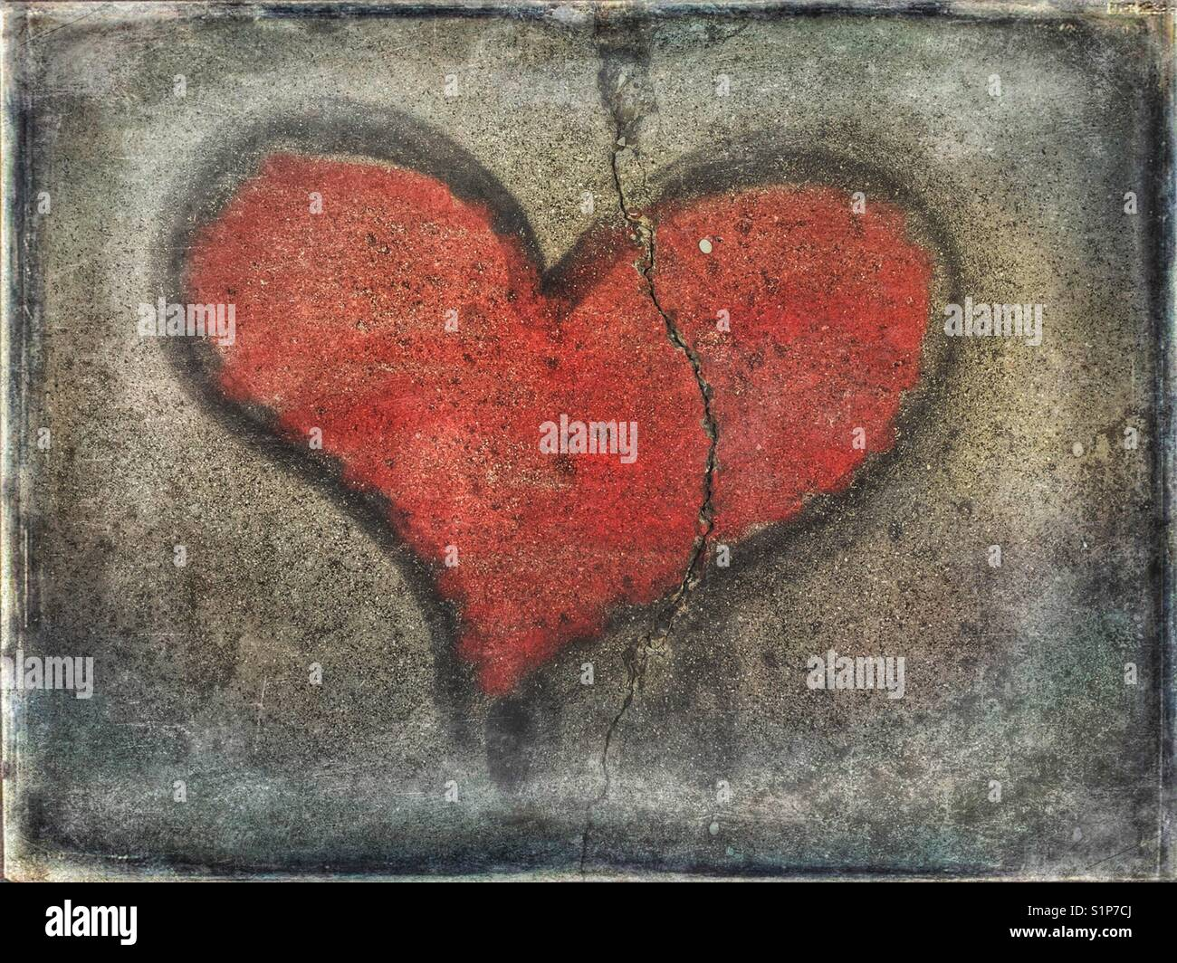 Red heart graffiti on cracked wall - Stock Image